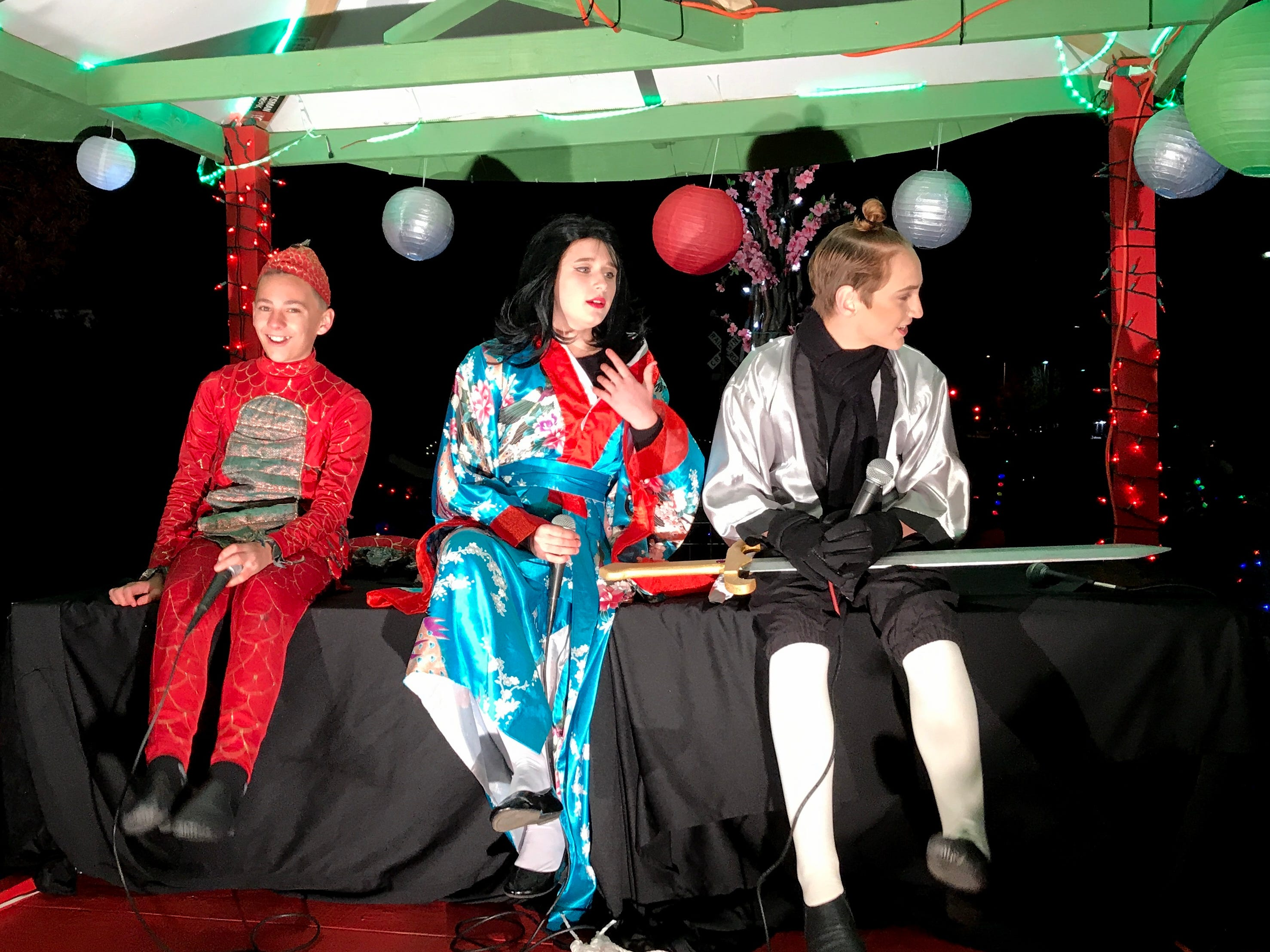 Mulan characters Noah Roberts, from left, Taylor Harper and Hayden Kay sit in the Redding School of the Arts float Saturday for the Lighted Christmas Parade.