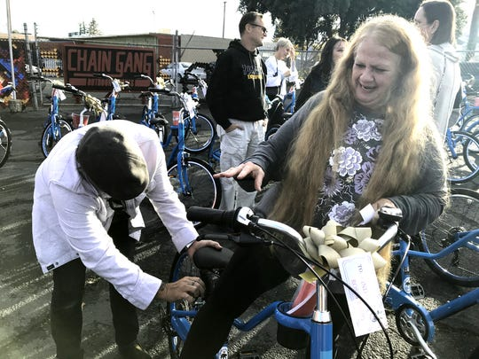 Tommy Keller, left, of the Giant Bicycles manufacturing company adjusts the seat for Linda Ross-Fraley, who received the free bike Saturday as part of a giveaway to 50 Carr Fire survivors.