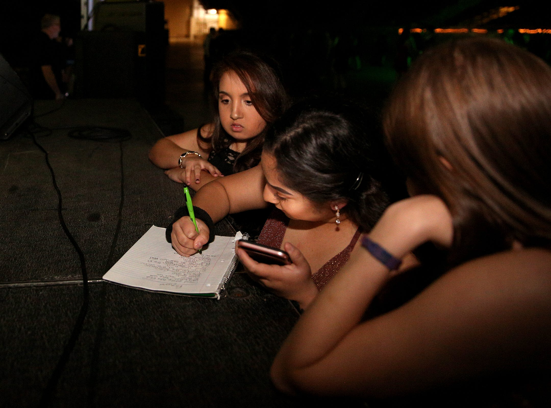 South Salem High School senior Janet Gonzalez (center) writes down requested songs during the annual SnoBall at the Oregon State Fairgrounds Pavilion in Salem on Saturday, Dec. 1, 2018. Gonzalez requested songs by rapper, YG.