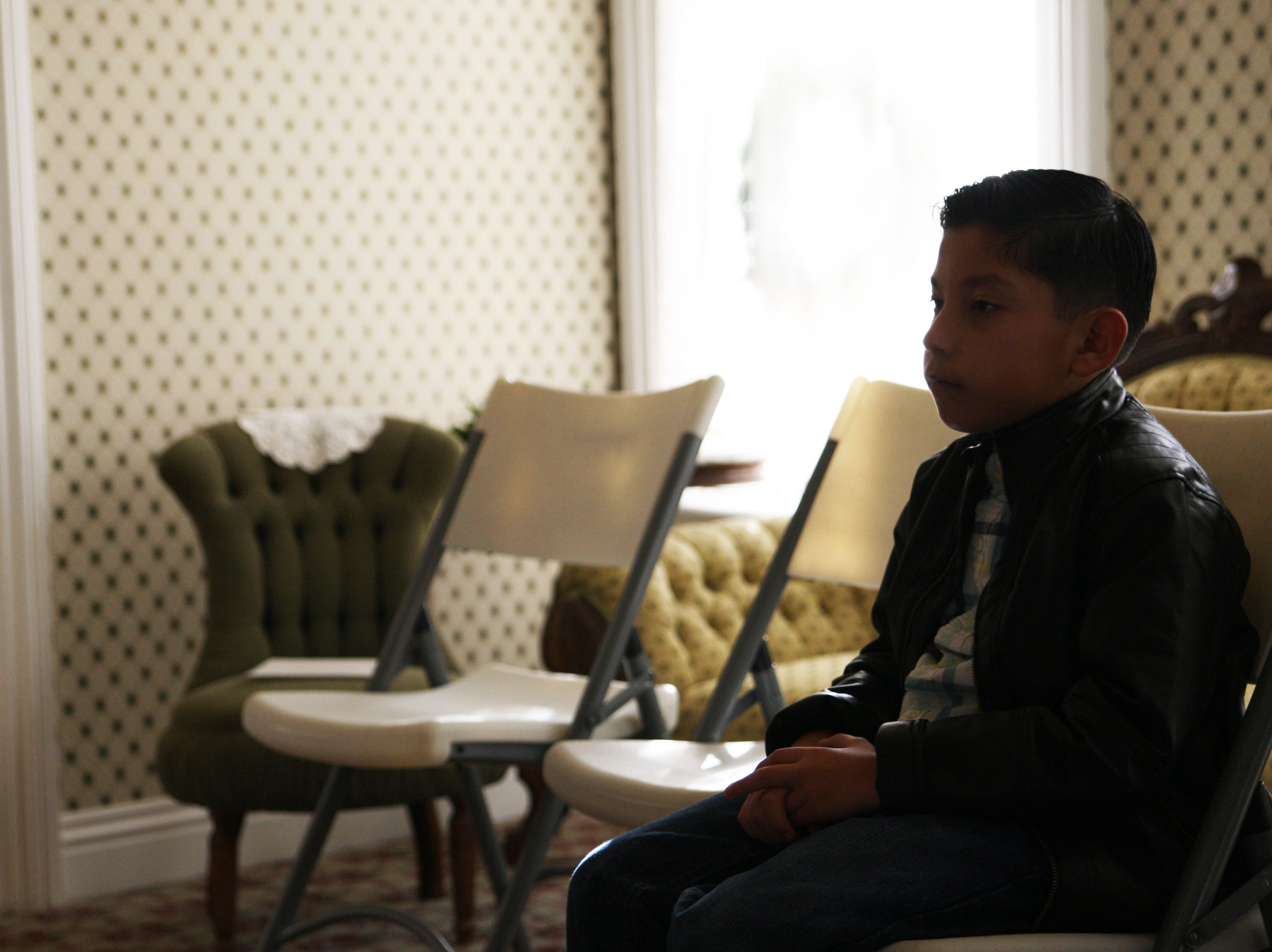 A boy sits and listens to the Christmas music in the Harvey house.
