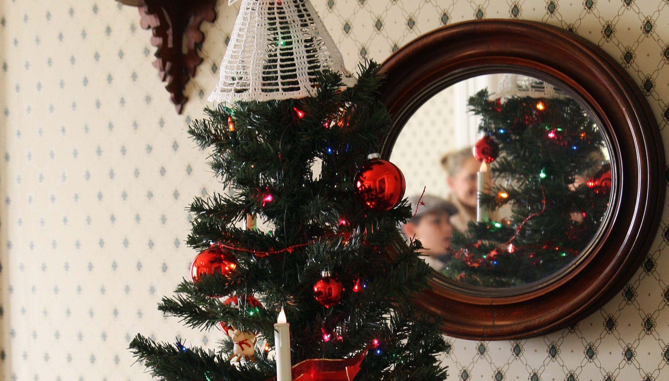 Hildur and Marcelo Avalos, captured in the mirror, gaze at the Christmas tree in the historic Harvey home.