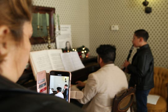 A woman films the musicians as they play plays Christmas carols on his clarinet at the historic Harvey home for the Christmas festivities.