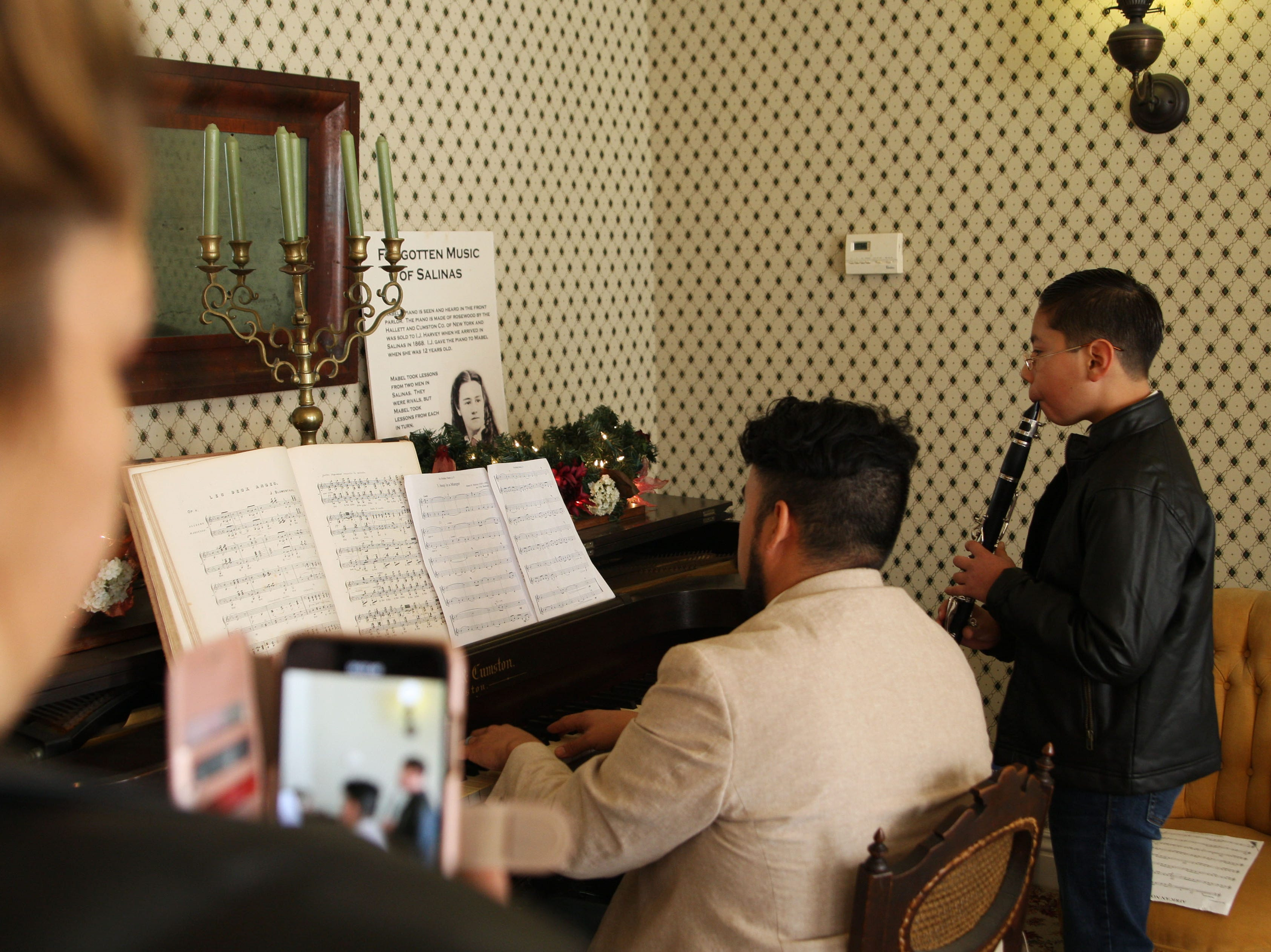 Local musicians play Christmas carols in the historic Harvey home. A woman films them.