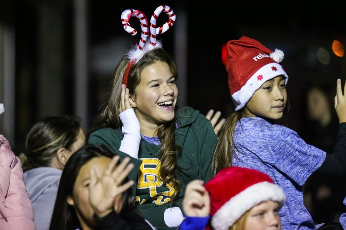 Kids on floats wave to spectators along Chadbourne Street for the Concho Christmas Celebration Parade Saturday Dec. 1, 2018, in downtown San Angelo.