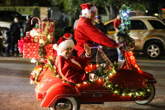 Participants wave to spectators along Chadbourne Street for the Concho Christmas Celebration Parade Saturday Dec. 1, 2018, in downtown San Angelo.