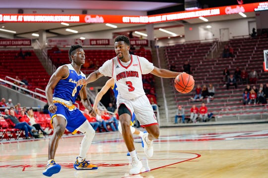 Tiston Simpson drives by Jarkel Joiner at the Sanford Coyote Sports Center on Saturday night in a 68-56 win over CSU Bakersfield.