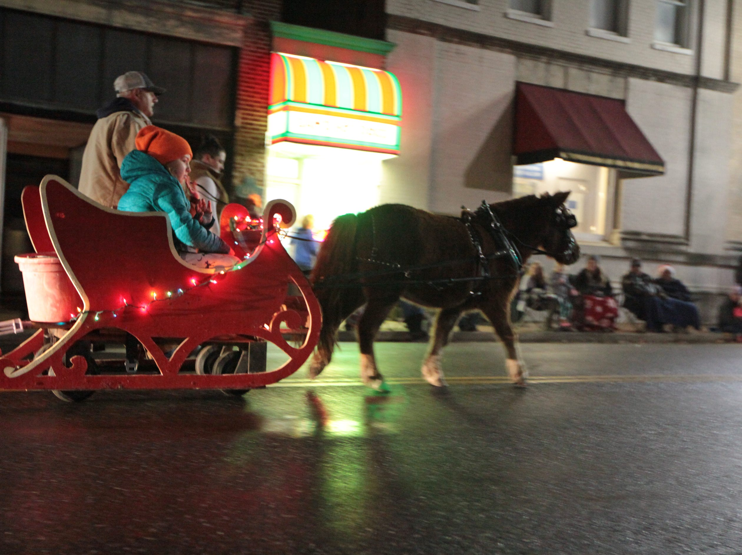 Participants in the annual Waynesboro Christmas parade travel up W. Main Street on Saturday, Dec. 1, 2018 tossing candy to patrons watching that evening.