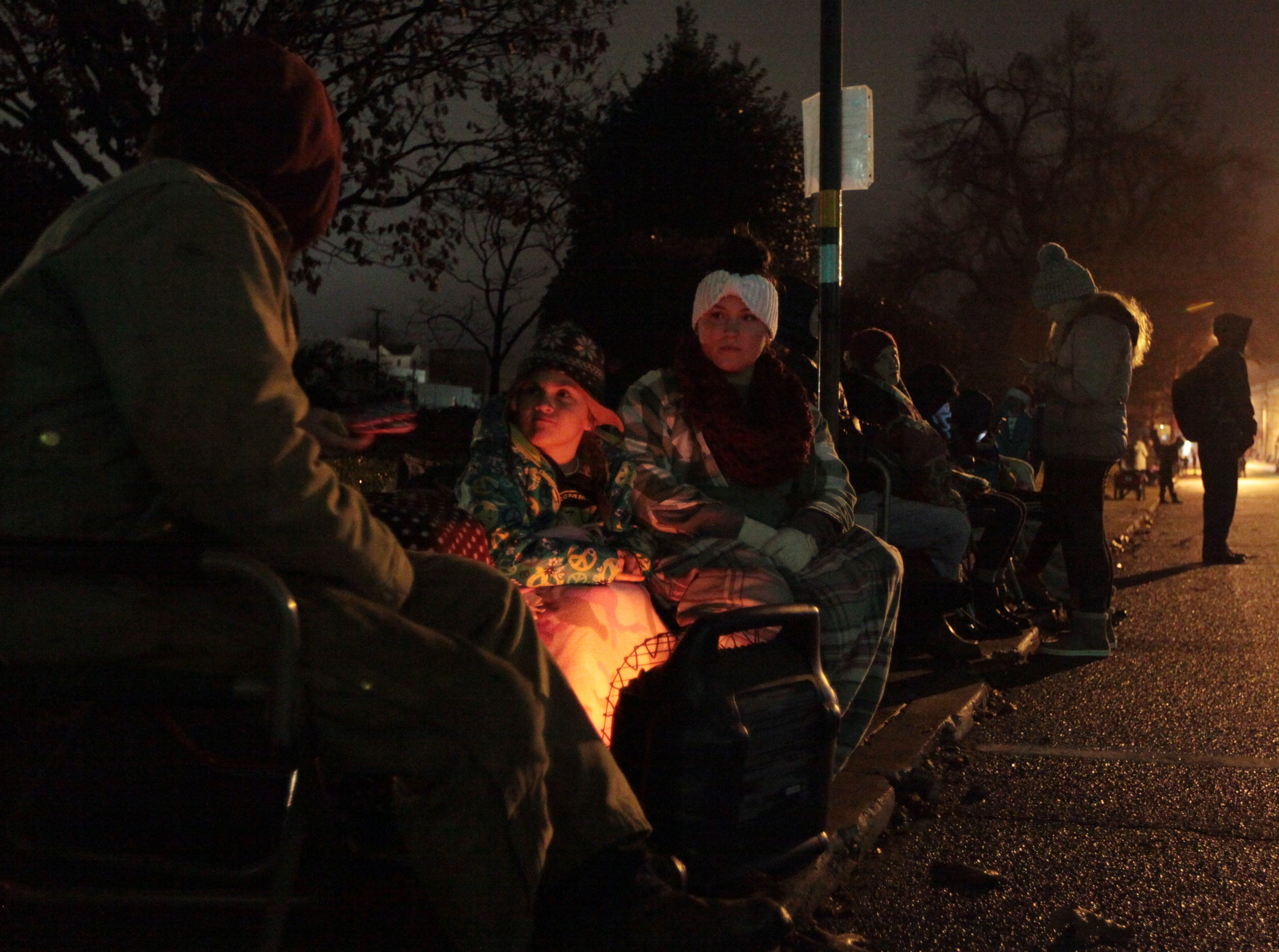 Whitney Ervin, center right, and daughter Keagan, center, 7, of Waynesboro sit with other family along Wayne Avenue to watch Waynesboro's annual Christmas parade on Saturday, Dec. 1, 2018.