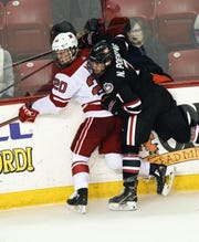 St. Cloud State's Nick Poehling check's Miami's Christian Mohs into the boards Saturday at Oxford, Ohio.