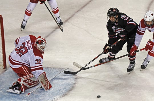 St. Cloud State's Jake Wahlin takes a swipe at the puck in front of Miami goalie Jordan Uhelski in the first period Saturday in Oxford, Ohio.