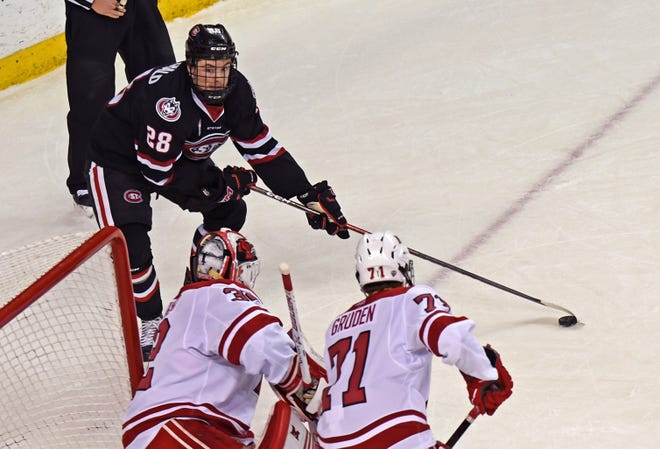 St. Cloud State's Blake Lizotte (28) tries to find an opening in front of Miami's net as goalie Jordan Uhelski and Jonathan Gruden in the first period Saturday at Oxford, Ohio. Lizotte scored the Huskies' first goal.