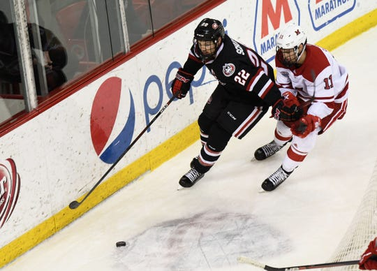 St. Cloud State's Jimmy Schuldt (22) fights for the puck with Miami's Rourke Russell in pursuit in the first period Saturday in Oxford, Ohio.