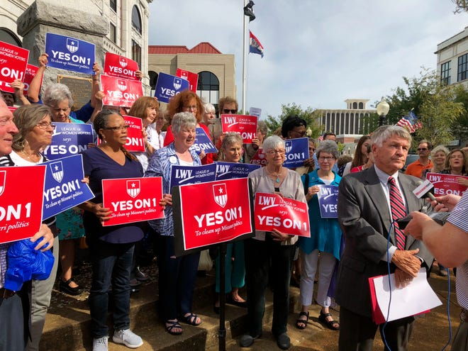 """FILE - In this Aug. 31, 2018 file photo, supporters of Missouri's redistricting ballot measure hold signs behind former state Sen. Bob Johnson as he serves as their spokesman during a press conference outside the Cole County Courthouse in Jefferson City, Mo. Voters approved Constitutional Amendment 1 on the Nov. 6 ballot. It is unique among redistricting reforms adopted by a number of states in recent years because it requires Missouri's state legislative districts to be drawn using a new mathematical formula to try to achieve """"partisan fairness"""" and """"competitiveness"""" after the 2020 Census. (AP Photo/David A. Lieb, File)"""