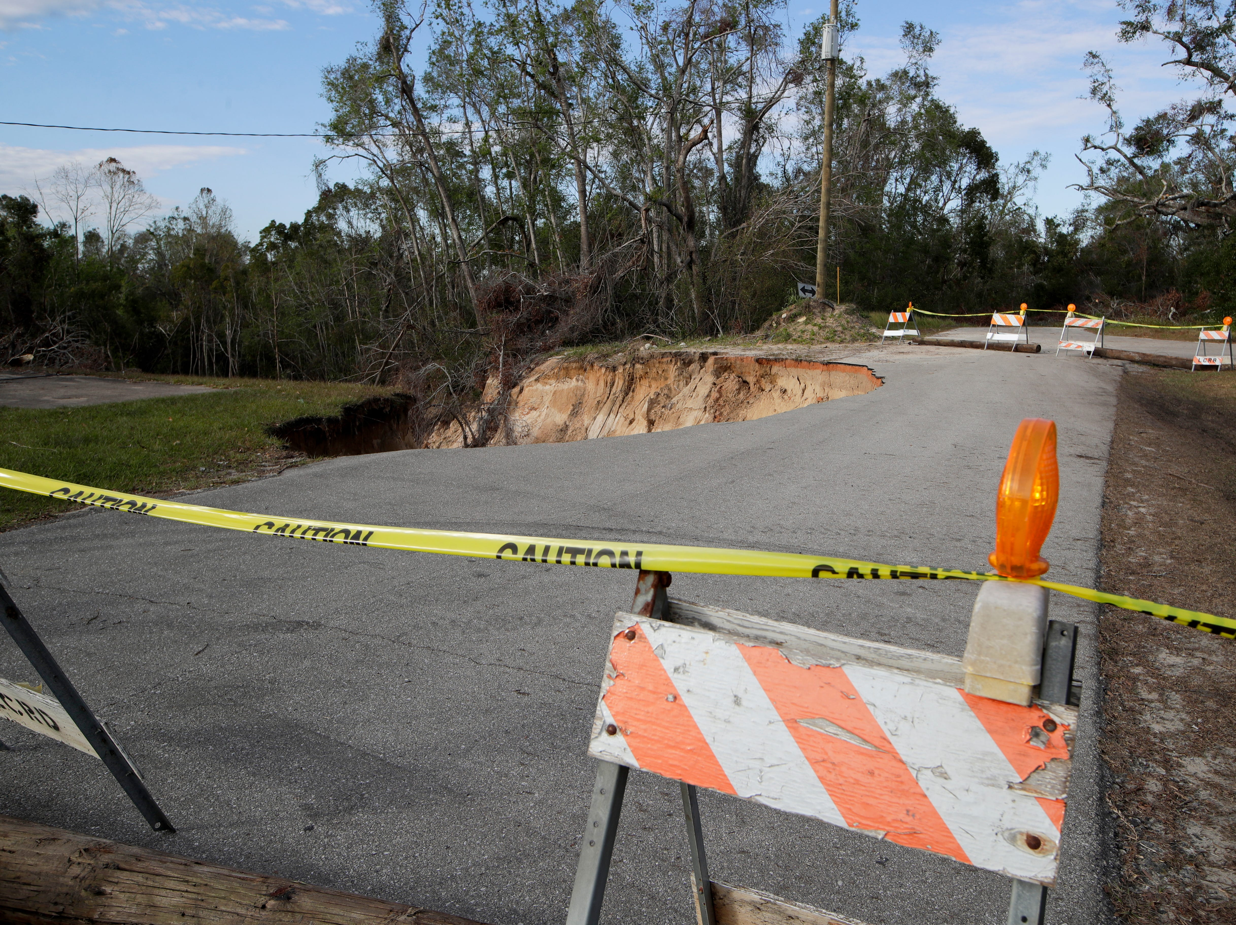The sinkhole that has swallowed nearly half of Virginia G. Weaver Street in Bristol, Fla. is partly blocked off by wooden poles and caution tape Friday, Nov. 30, 2018.