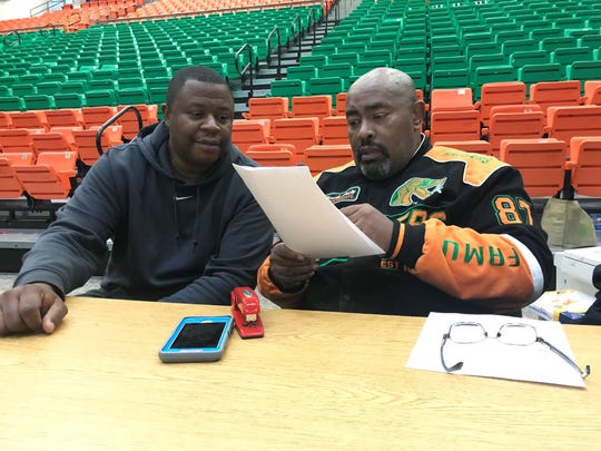 FAMU assistant sports information director Alvin Hollins (left) reviews stats from a women's basketball game with sports information director Vaughn Wilson.