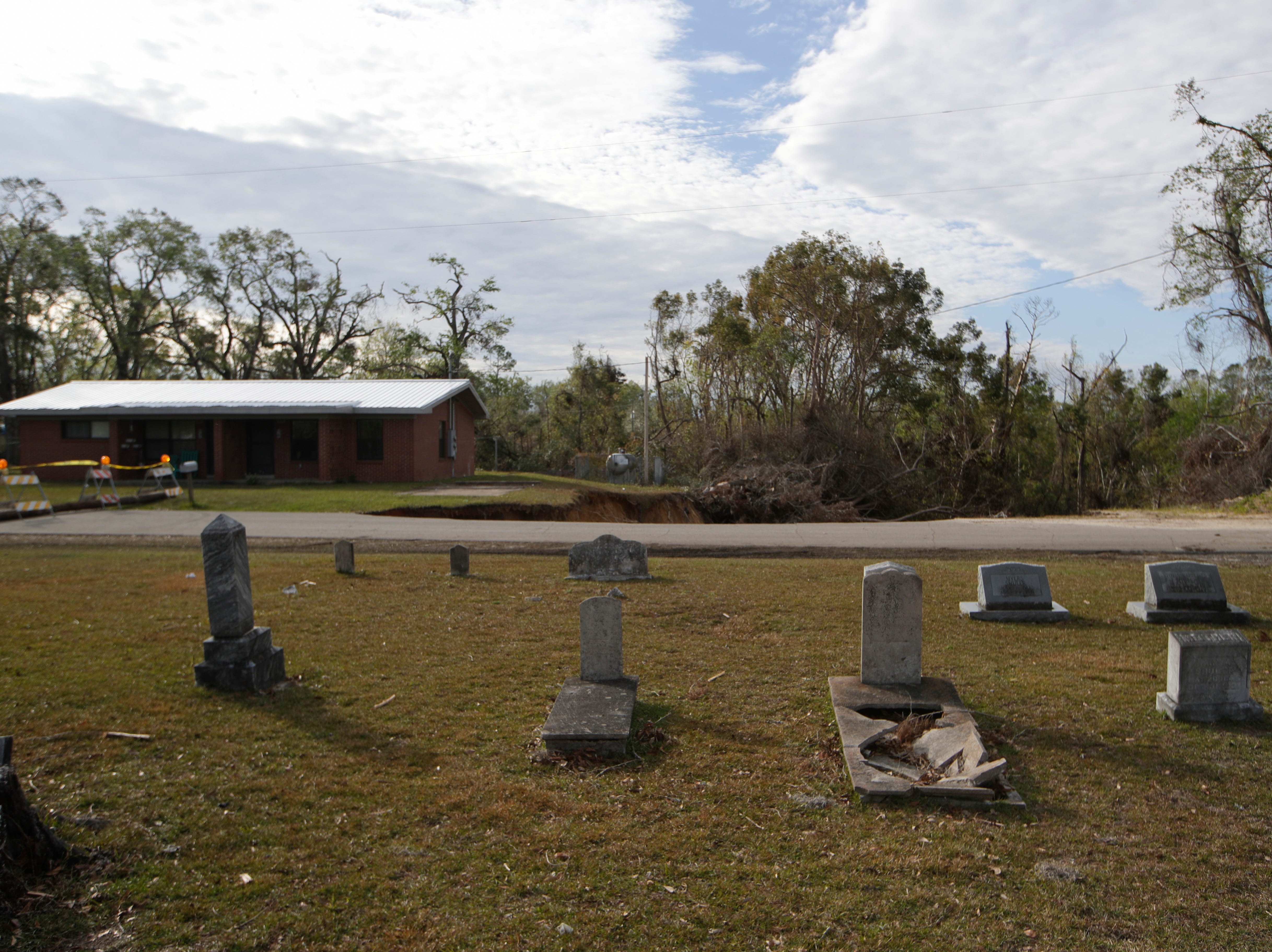 A cemetery begins just across the road from where a giant hole has swallowed half of Virginia G. Weaver Street in Bristol, Fla. Friday, Nov. 30, 2018.