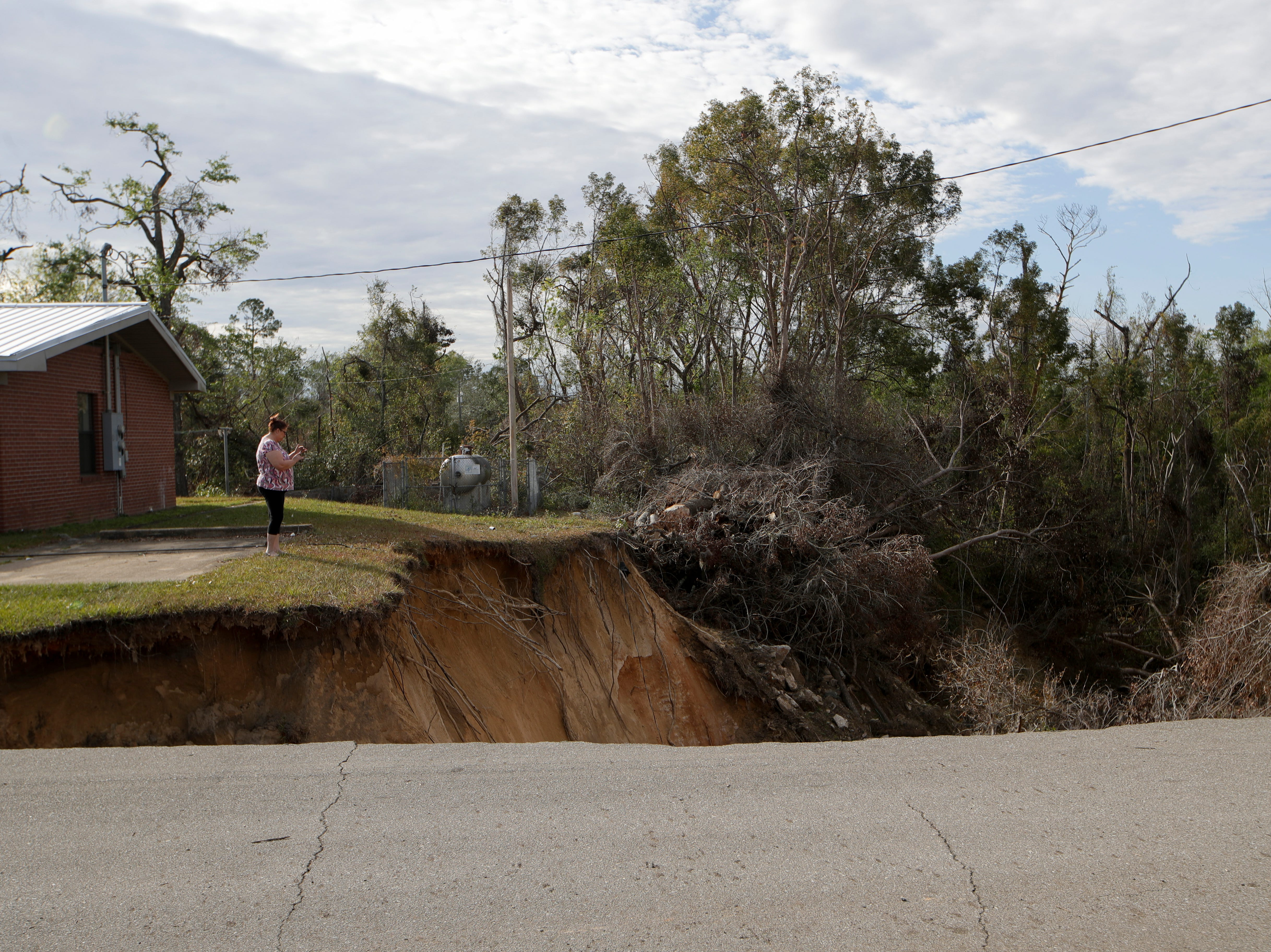 Brenda Peterson stops by the giant hole on Virginia G. Weaver Street in Bristol, Fla. on her way home from work to take a look at the giant hole that has opened up there Friday, Nov. 30, 2018.
