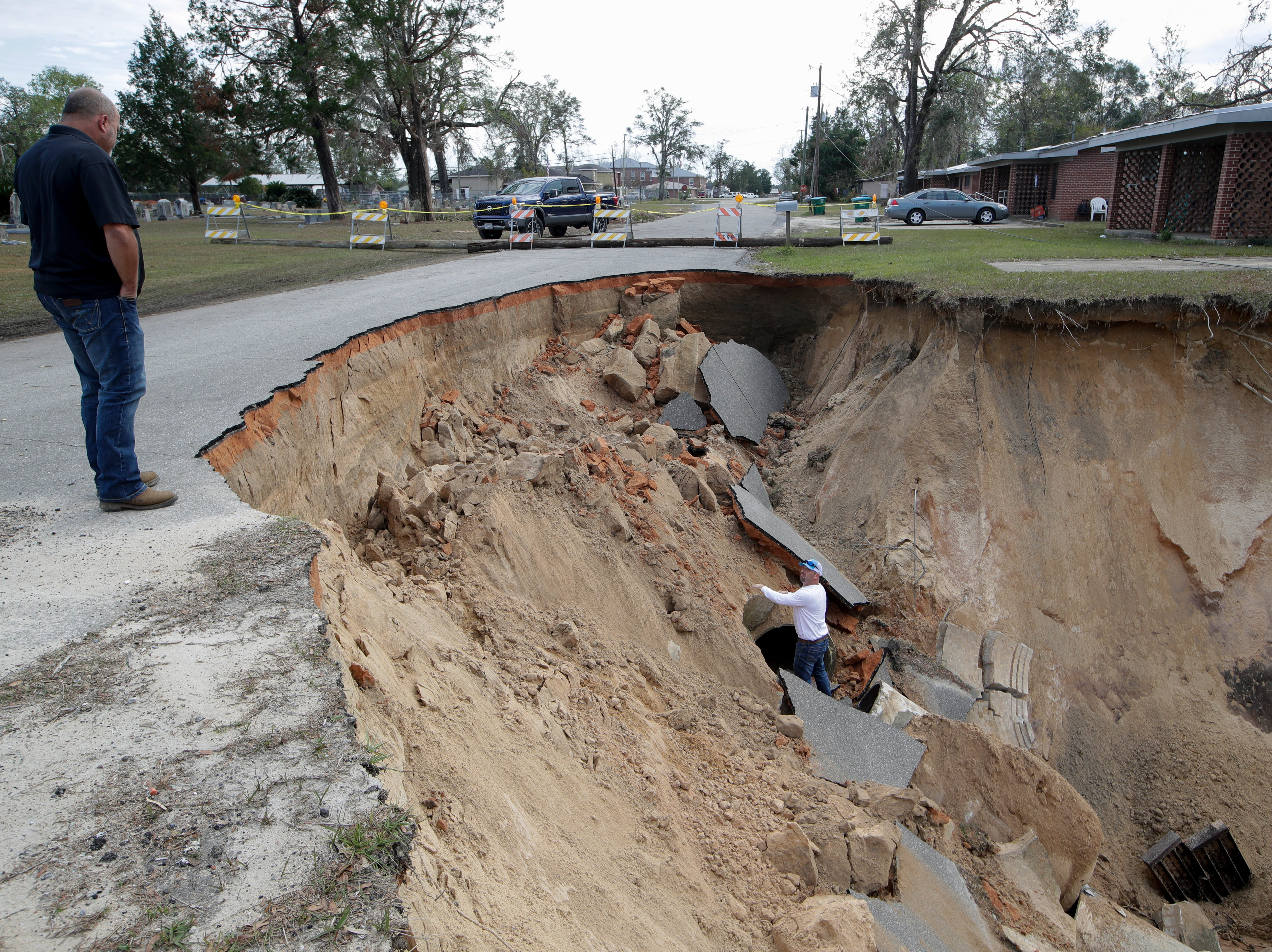 Hale Contracting Inc. Superintendent Jamie Stone, left and  Project Manger Del Tucker stop by the giant hole on Virginia G. Weaver Street in Bristol, Fla. that they will begin working to repair next week, Friday, Nov. 30, 2018.