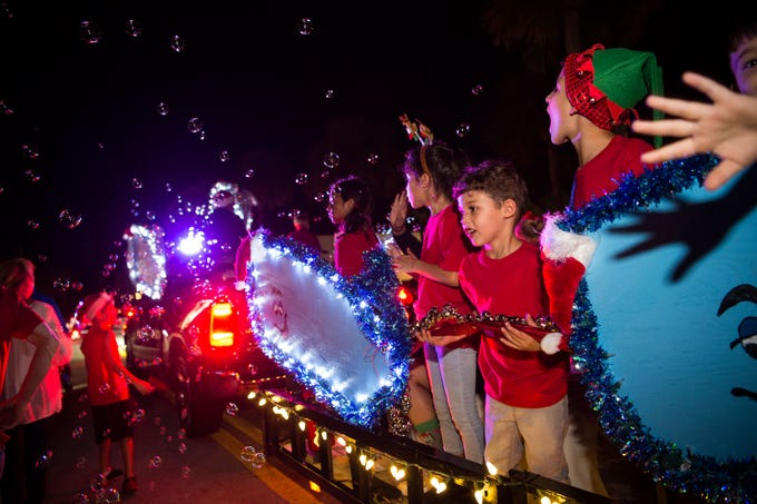 Michael Gonzalez (right of center), 4, of Vero Beach, rides on the Vatland Honda float and jingles bells during the 34th annual Centennial Christmas Parade along Ocean Drive on Saturday, Dec. 1, 2018, in Vero Beach. The fourth annual Candy Cane 3K preceded the parade.