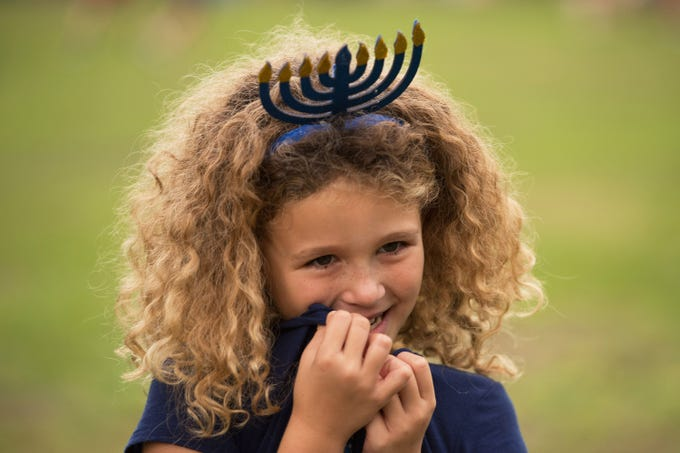 "Delaney Readling, 7, of Jensen Beach, shares a light moment with her friend Rachel Linda, 8, of Palm City, (not pictured) during the 21st annual Community Chanukah Celebration and public Menorah Lighting Ceremony hosted by the Chabad Jewish Community Center of Martin and St. Lucie County at Memorial Park on Sunday, December 2, 2018 in Stuart. ""It's really fun,"" said Reading about coming out to celebrate Chanukah."