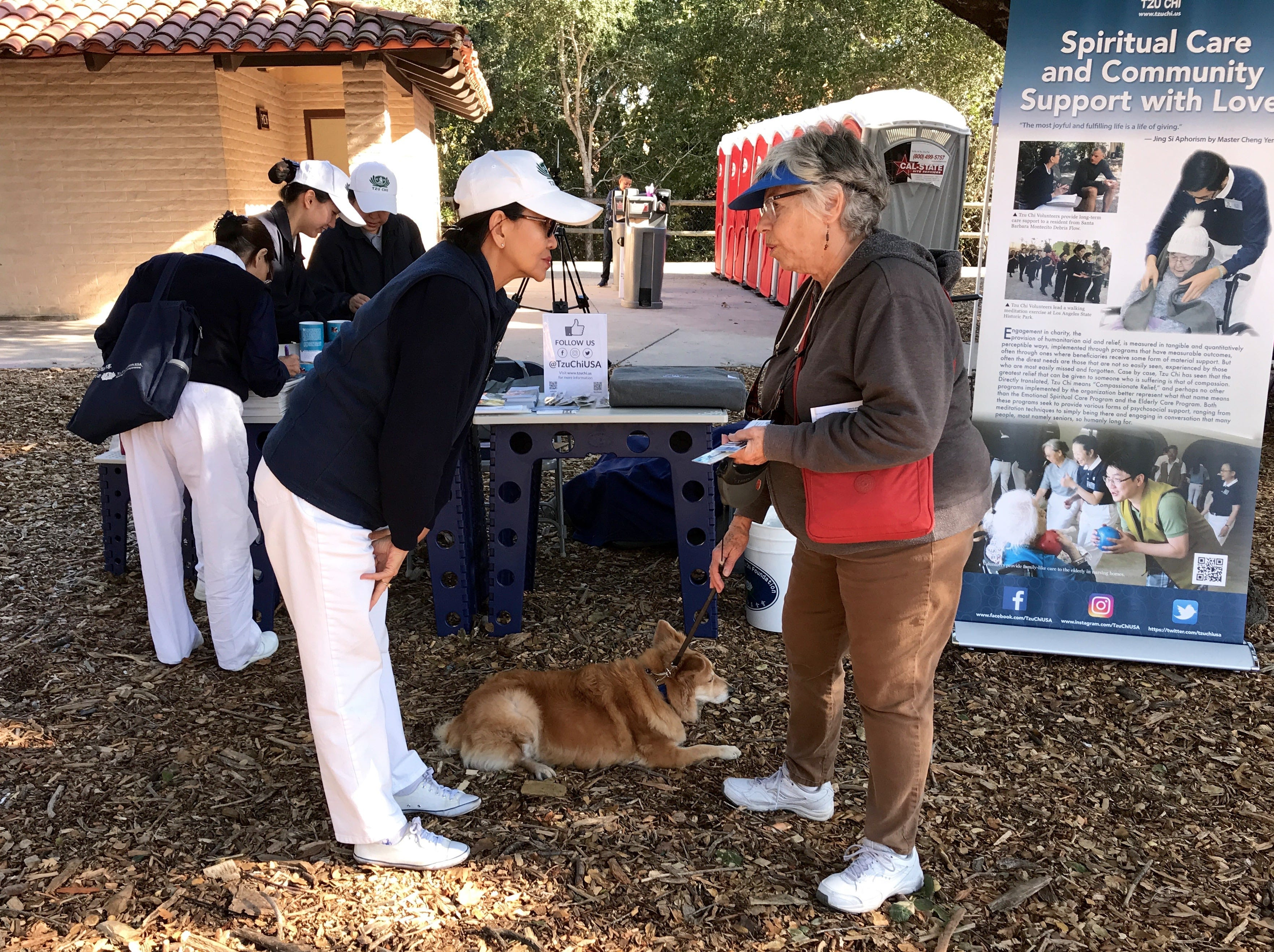 April Goddard, left, a volunteer with the Tzu Chi foundation speaks with Vivian S., of Ojai, a former Thomas Fire evacuee, about her hearing dog, Cami.  The foundation is helping support families affected by California's wildfires.