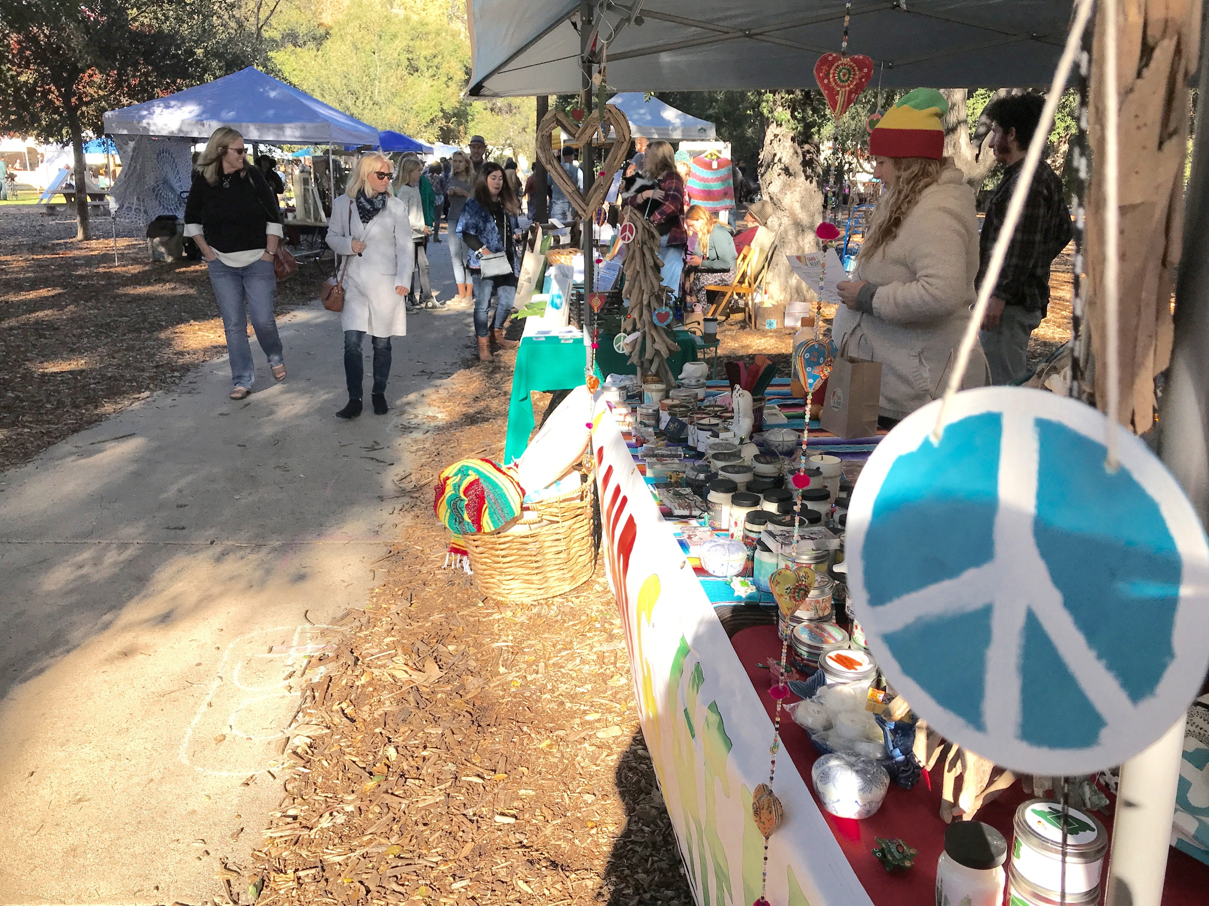 People browse stands of wares sold by artists affected by the Thomas Fire during Saturday's one-year remembrance event.