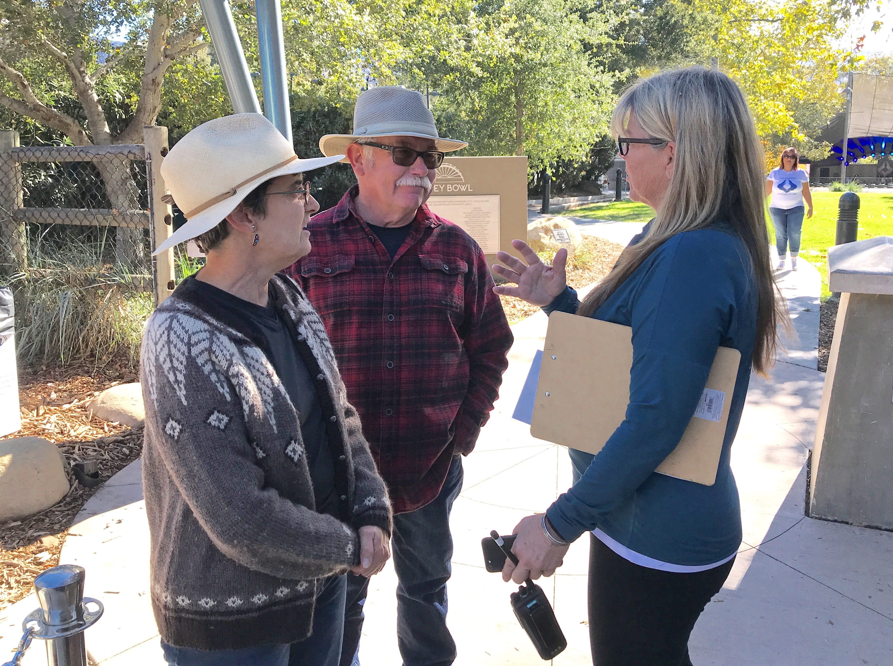 Organizer Kat Merrick, right, speaks with Bob and Heather Sanders, who lost their Upper Ojai home in the Thomas Fire.