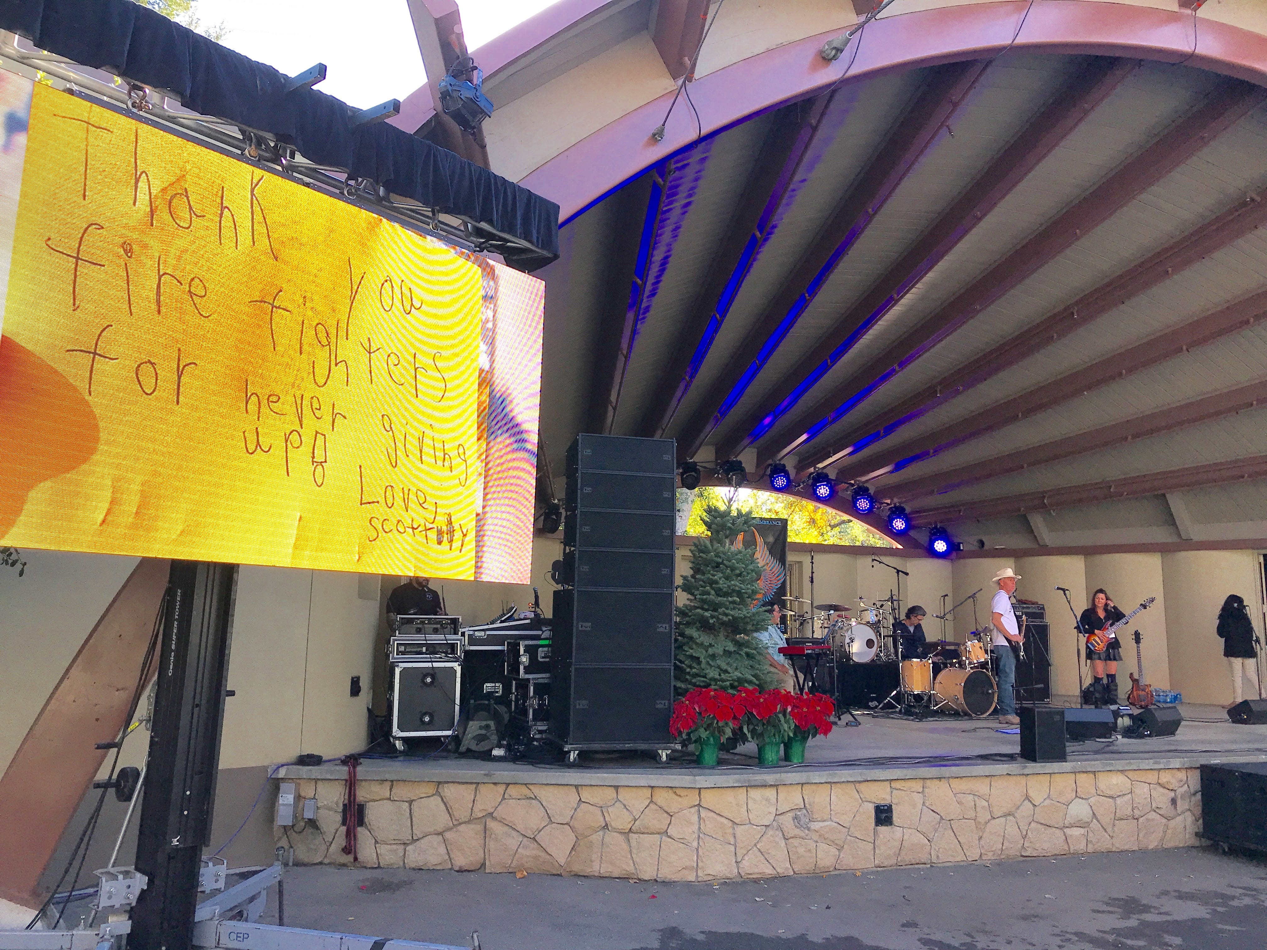 A thank you note to firefighters is displayed as part of a slideshow about the Thomas Fire, while the band Charles Law warms up for a concert at Libbey Bowl on Saturday.