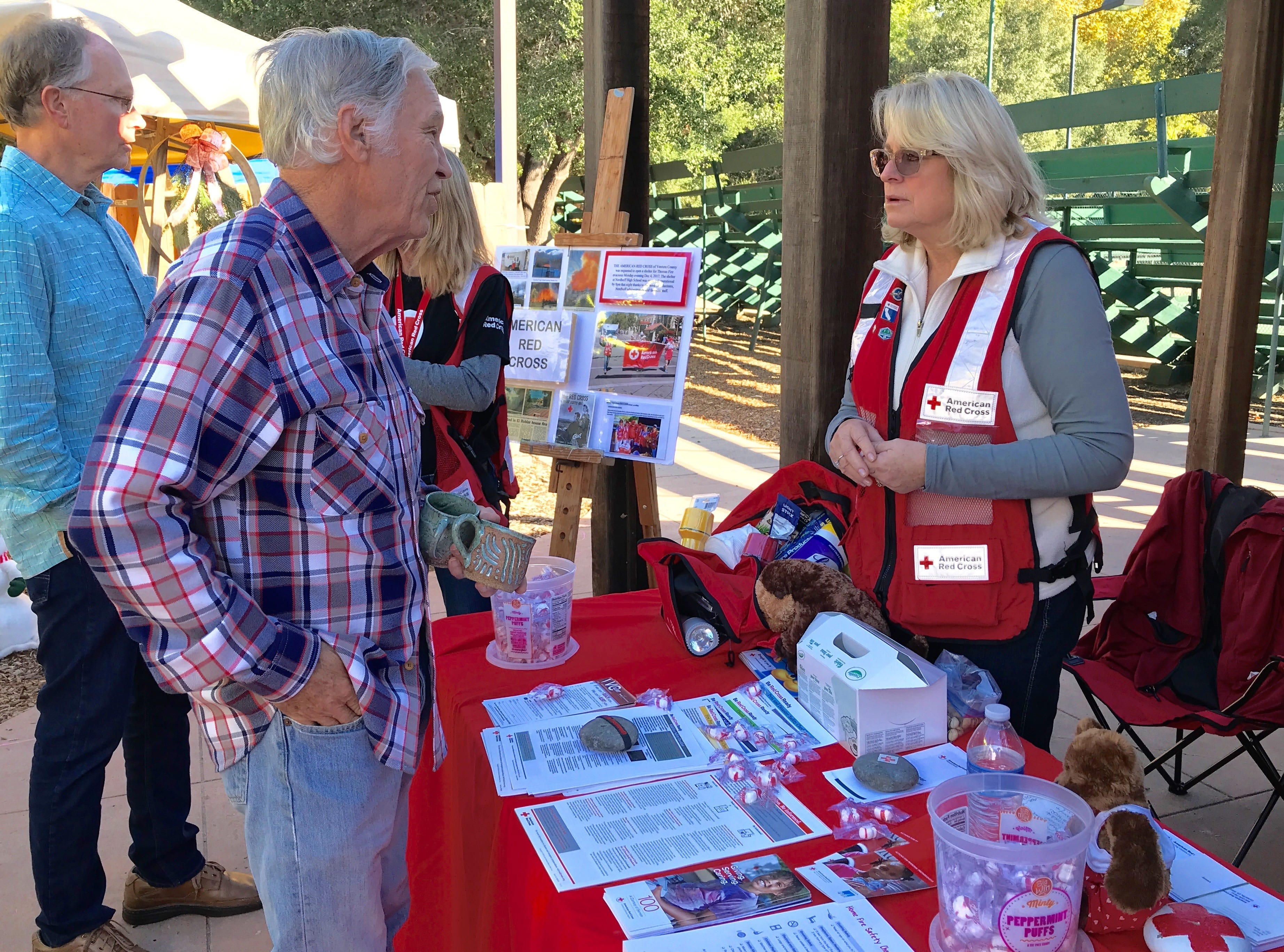 Red Cross volunteer Cindy Anderson speaks with Ojai resident Terry Mahurin at a booth set up for the 1 Year Thomas Fire Remembrance Event at Libbey Park on Saturday.