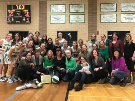 Irvington head coach Gina Maher poses with current and former players underneath the banner commemorating her 700th career win on Dec. 1, 2018.