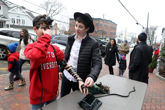 Seth Kissel, 13, left, of Cortlandt recites a prayer Sunday after Ari Schmukler, 16, helped him put on tefillin, a Jewish mitzvah to connect the heart and mind to God, at the Hanukkah Village event in Irvington.