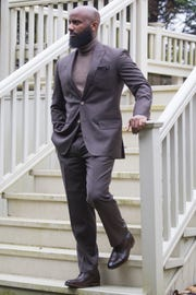 Robert Redden-Huff wears a chocolate brown 150s suit by Sam Surin; cashmere turtleneck by Nordstrom; houndstooth wool pocket square by Armstrong & Wilson from Nordstrom; and dark brown Oxford shoes by Cole Haan.