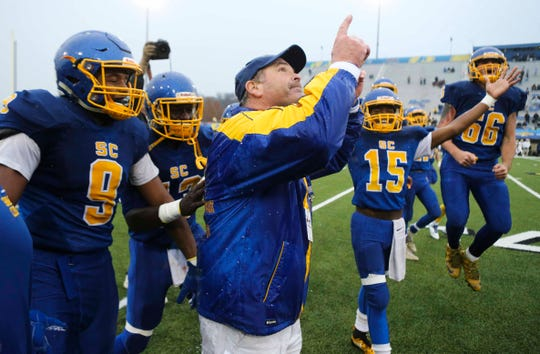 Sussex Central head coach John Wells shares the celebration with his players as the Golden Knights' beat Salesianum 33-7 to win the DIAA Division I state tournament championship game at Delaware Stadium Saturday.