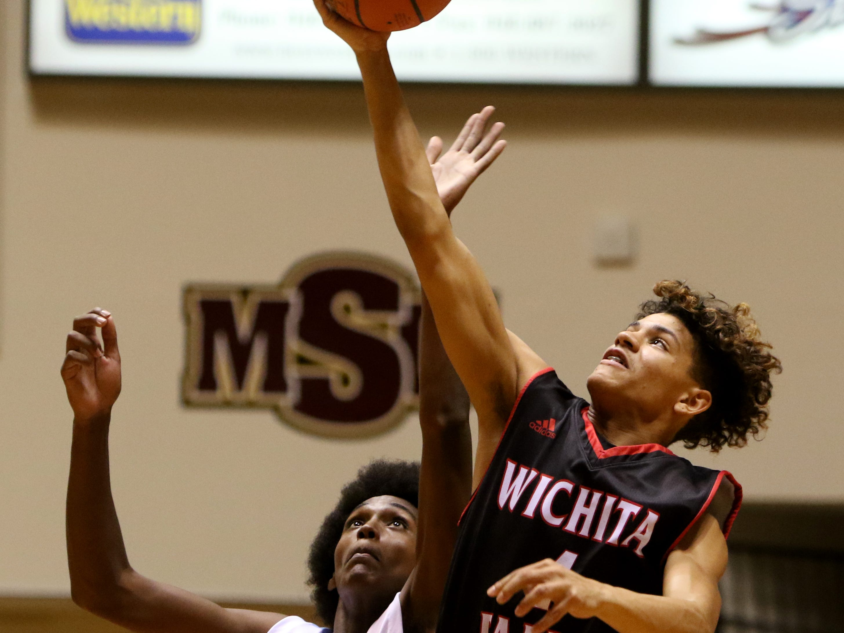 Wichita Falls High School's Leon Dennis reaches the jump ball before Hirschi's Gabe Colbert in the Wichita Falls Classic Saturday, Dec. 1, 2018, in D.L. Ligon Coliseum at Midwestern State University.