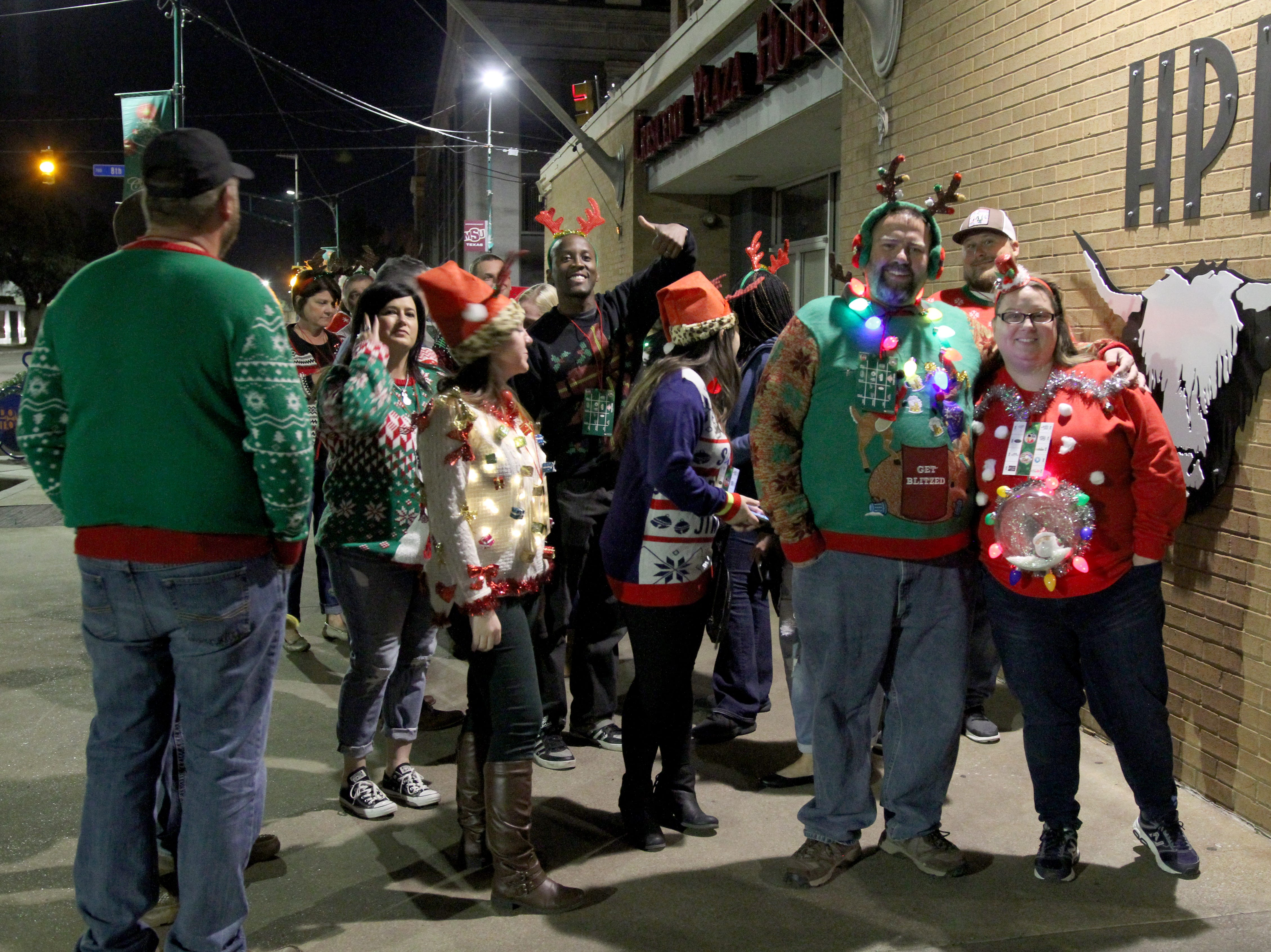 People wait to get inside Highlander Public House on their first stop on Rudolph's First Ugly Sweater Crawl Saturday, Dec. 1, 2018, in Downtown Wichita Falls.