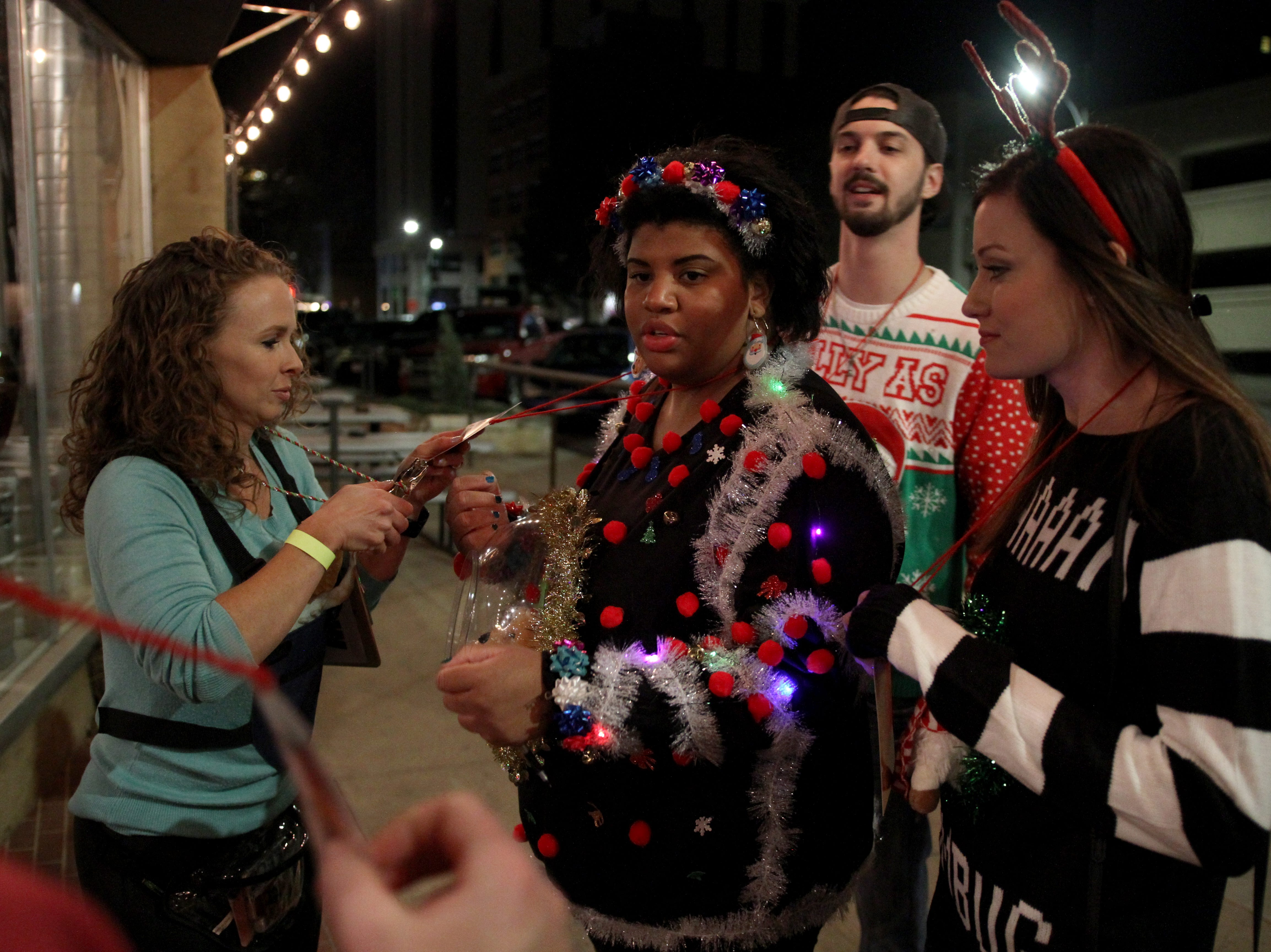 Stormi Arnold punches Kayla Reid card outside Wichita Falls Brewing Company during Rudolph's First Ugly Sweater Crawl Saturday, Dec. 1, 2018, in Downtown Wichita Falls.