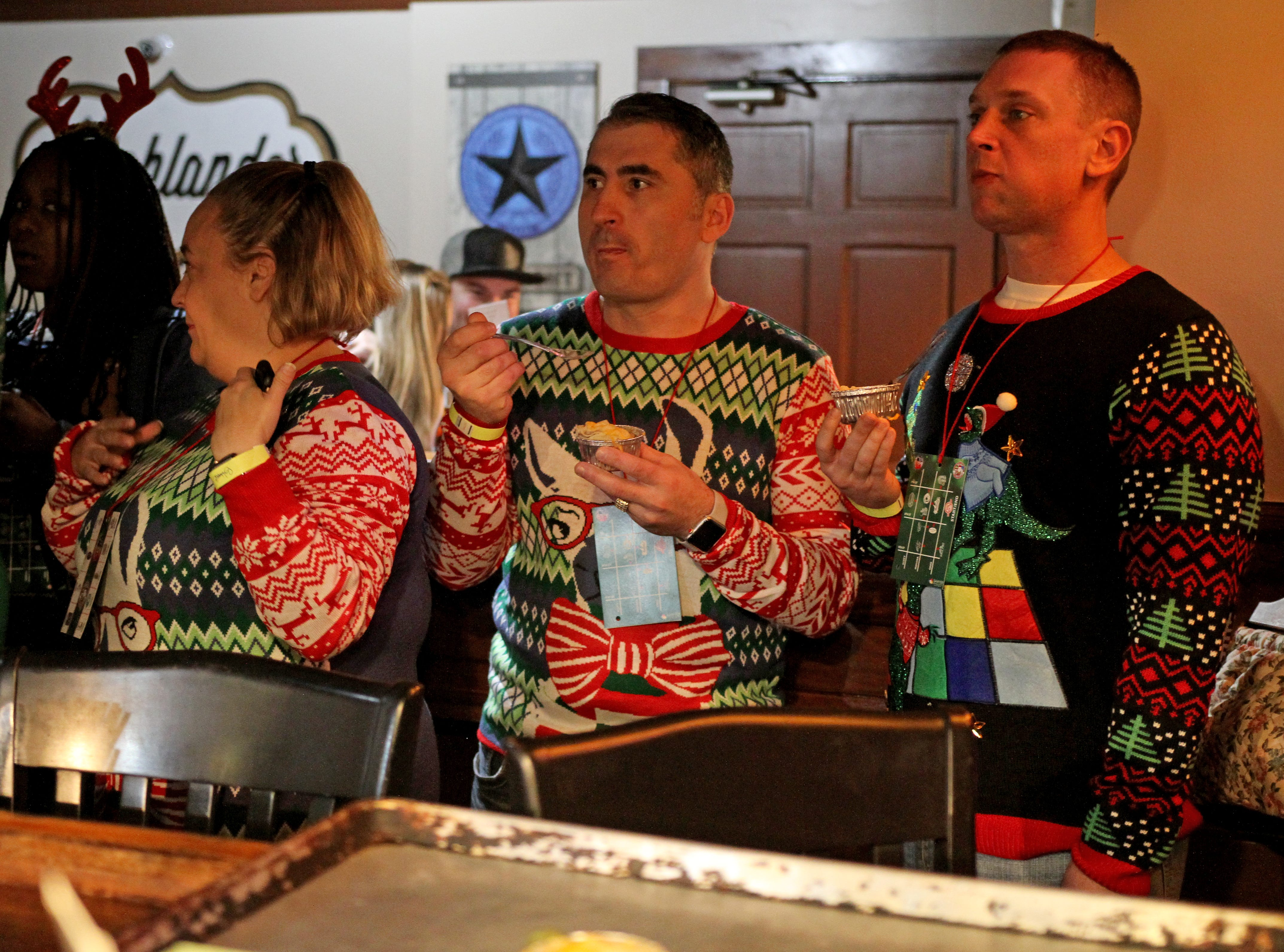 People eat while at their first stop at Highlander Public House on Rudolph's First Ugly Sweater Crawl Saturday, Dec. 1, 2018, in Downtown Wichita Falls.