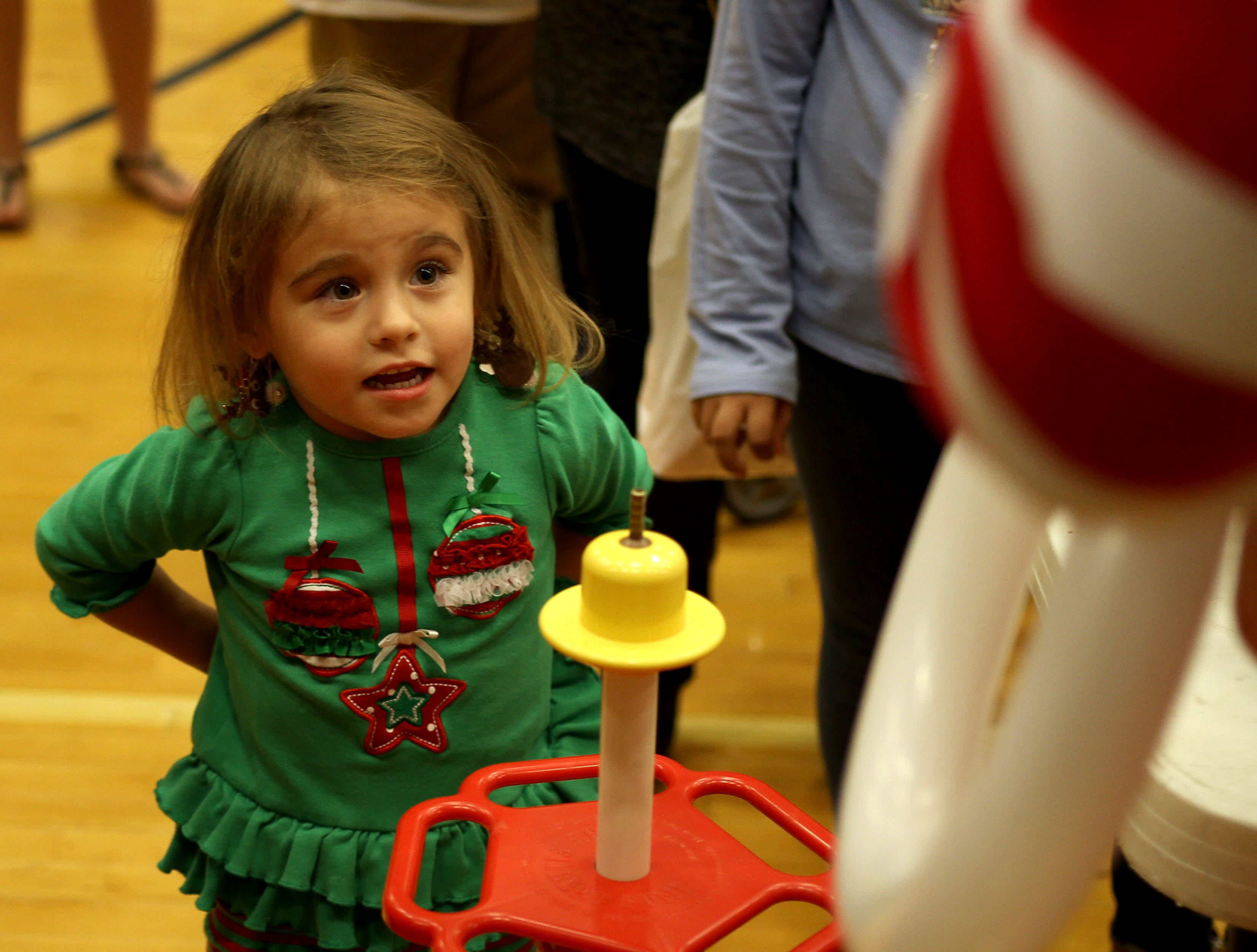 Jade Gunder watches as her ballon hat is made at the Wichita Falls Parks and Recreation Christmas in the Park Saturday, Dec. 1, 2018, at the Scotland Park Elementary School gym.