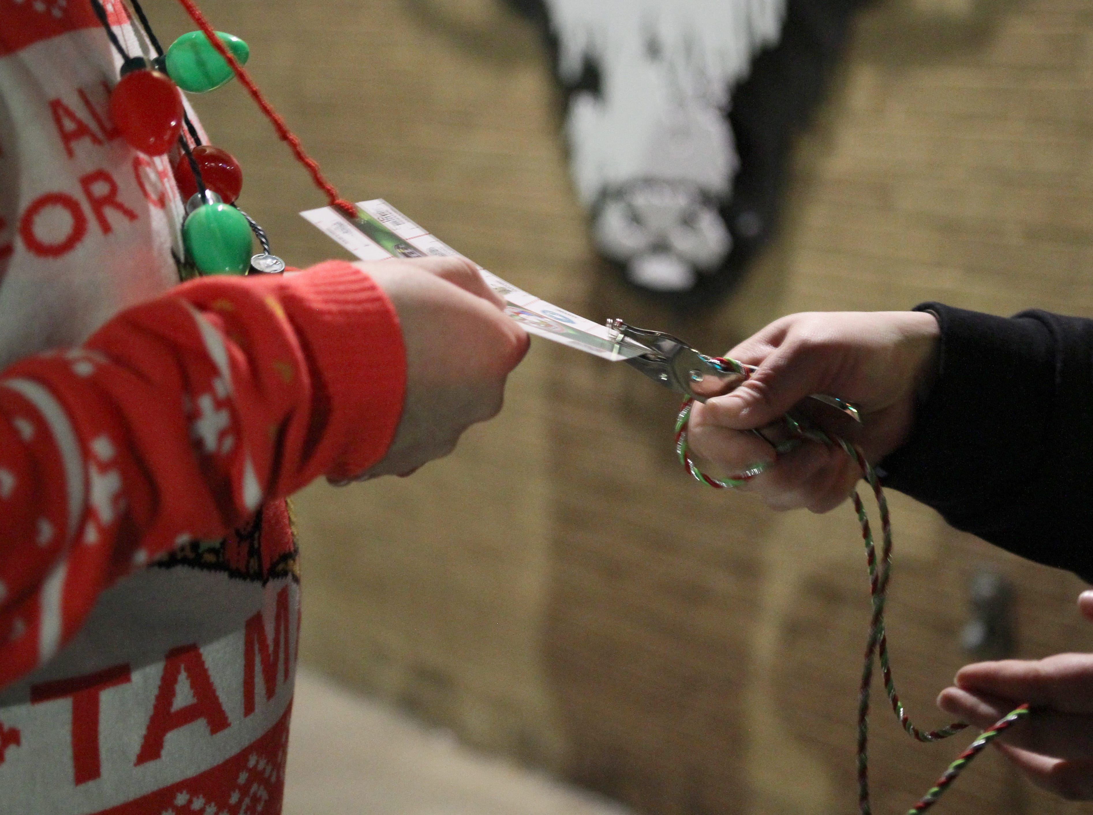 People have their cards punch at their first stop at Highlander Public House on Rudolph's First Ugly Sweater Crawl Saturday, Dec. 1, 2018, in Downtown Wichita Falls.