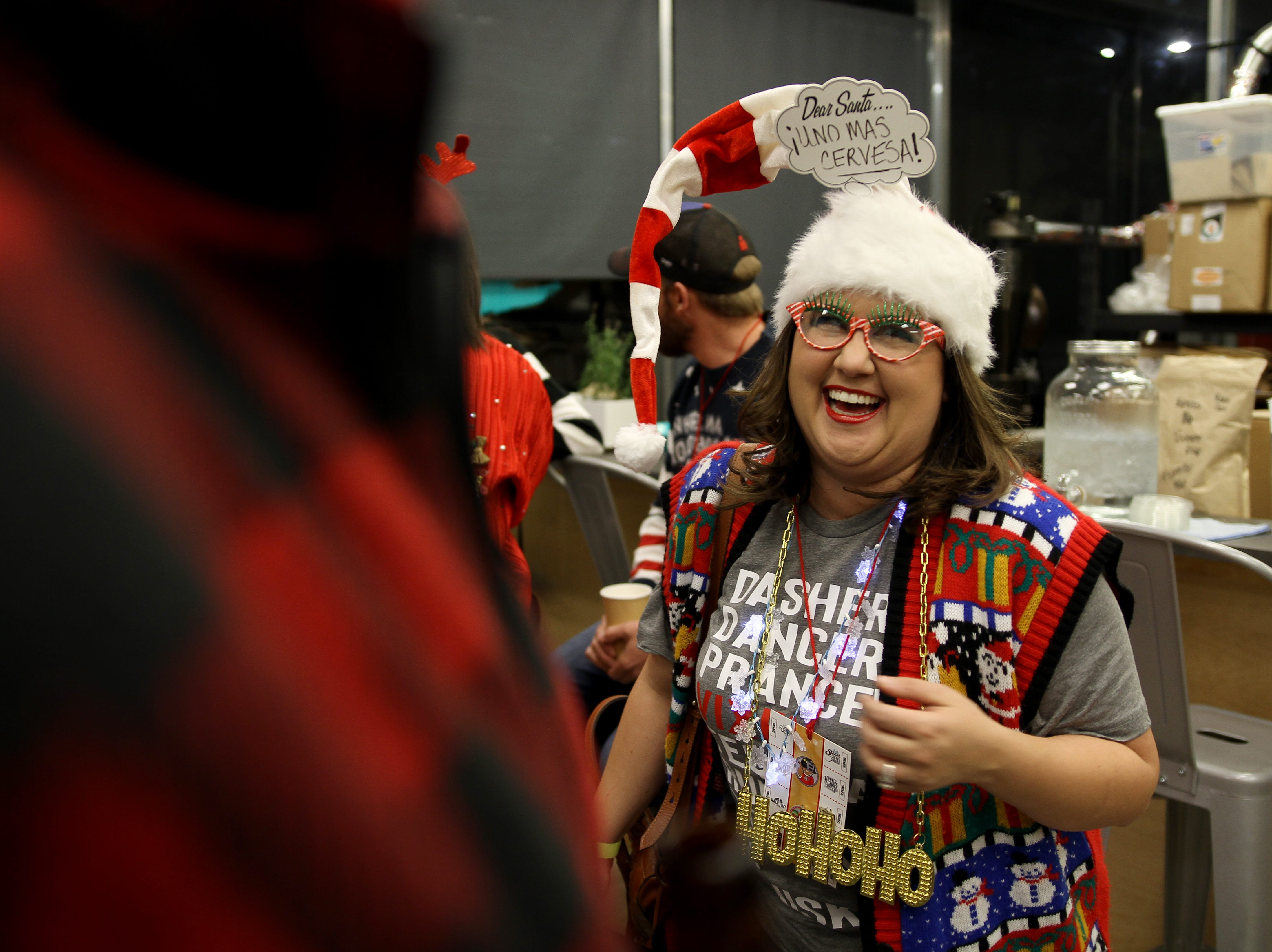 April Beck laughs while talking with Ross Hammond at Rudolph's First Ugly Sweater Crawl Saturday, Dec. 1, 2018, in Odd Duck Coffee.