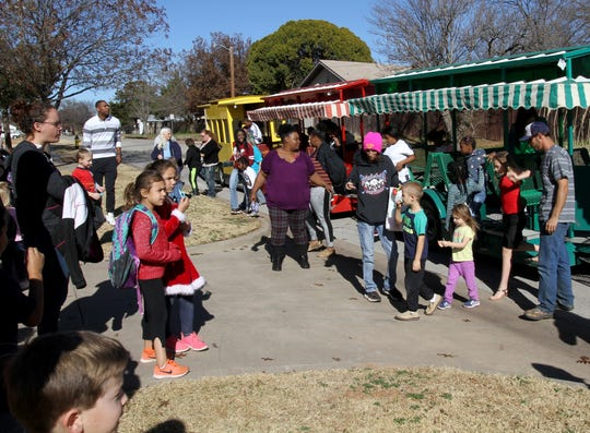 In this file photo, people wait to board the train at the Wichita Falls Parks and Recreation Christmas in the Park at the Scotland Park Elementary School gym.