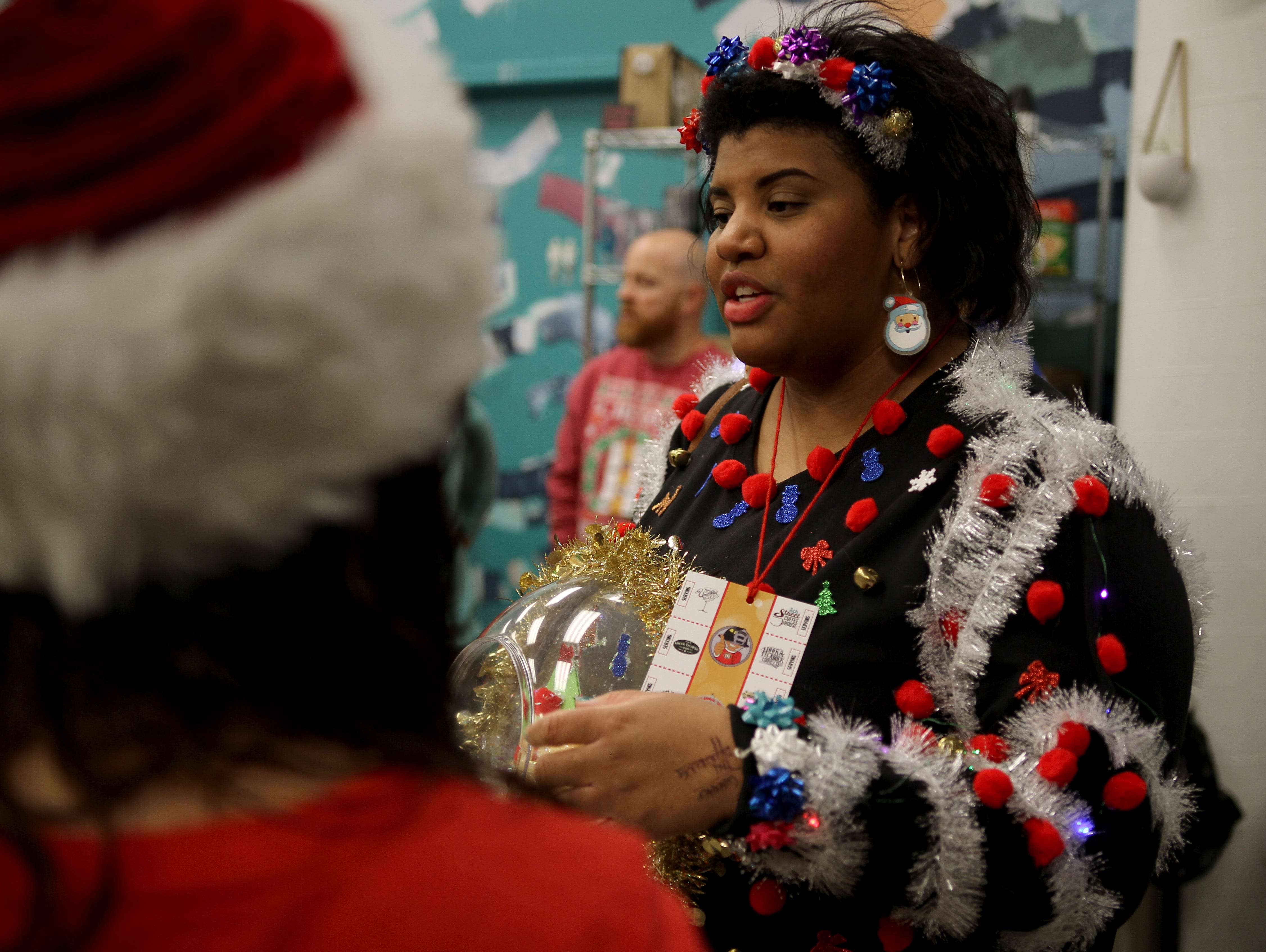 Kayla Reid mingles with her group at Rudolph's First Ugly Sweater Crawl Saturday, Dec. 1, 2018, in Odd Duck Coffee.