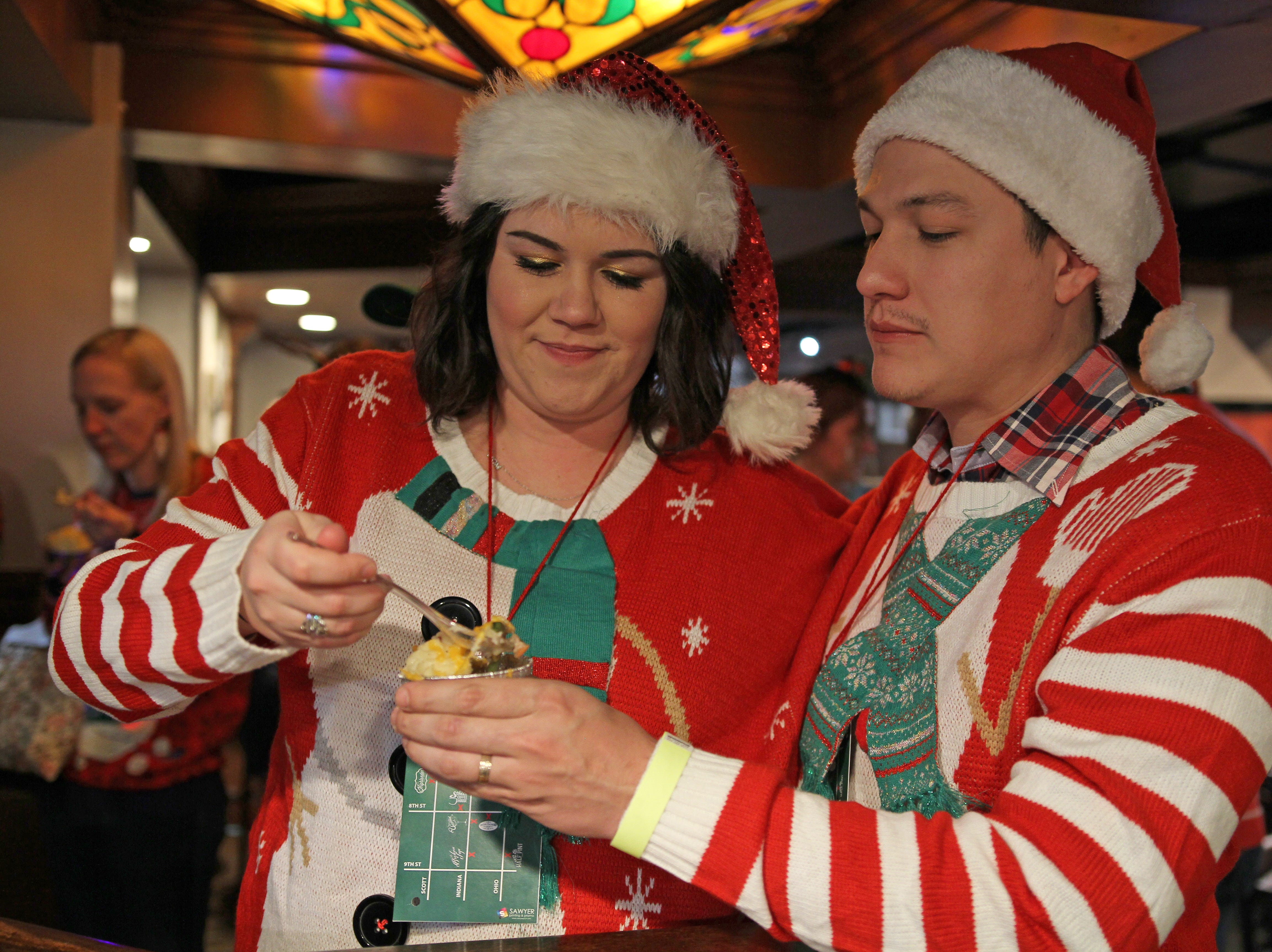 Tori and Chris Sosa eat at their first stop on Rudolph's First Ugly Sweater Crawl Saturday, Dec. 1, 2018, in the Highlander.