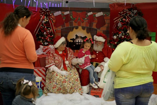 In this file photo, kids get their picture taken with Santa and Mrs. Claus at the Wichita Falls Parks and Recreation Christmas in the Park at the Scotland Park Elementary School gym.