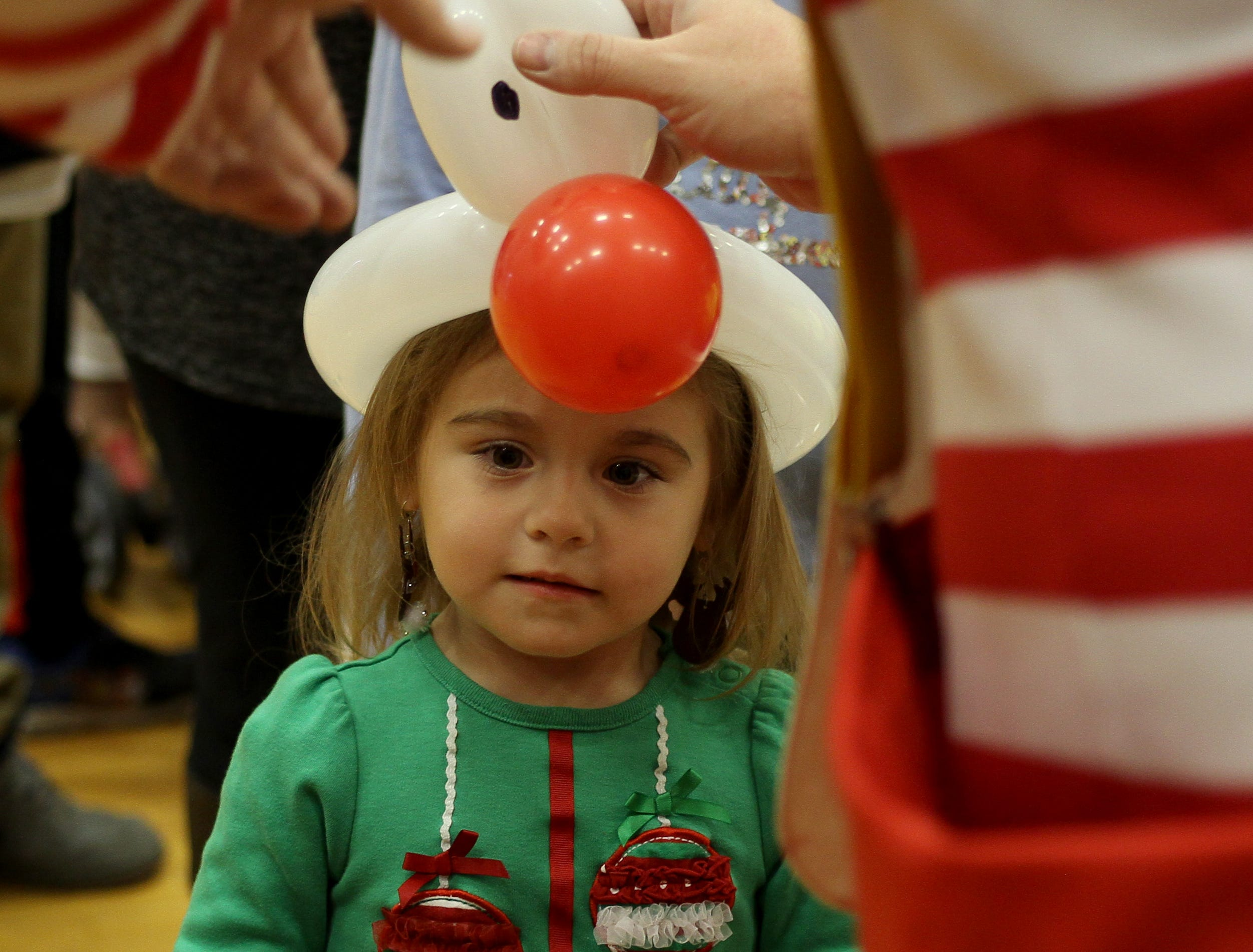 Jade Gunder is given a Rudolph ballon hat at the Wichita Falls Parks and Recreation Christmas in the Park Saturday, Dec. 1, 2018, at the Scotland Park Elementary School gym.