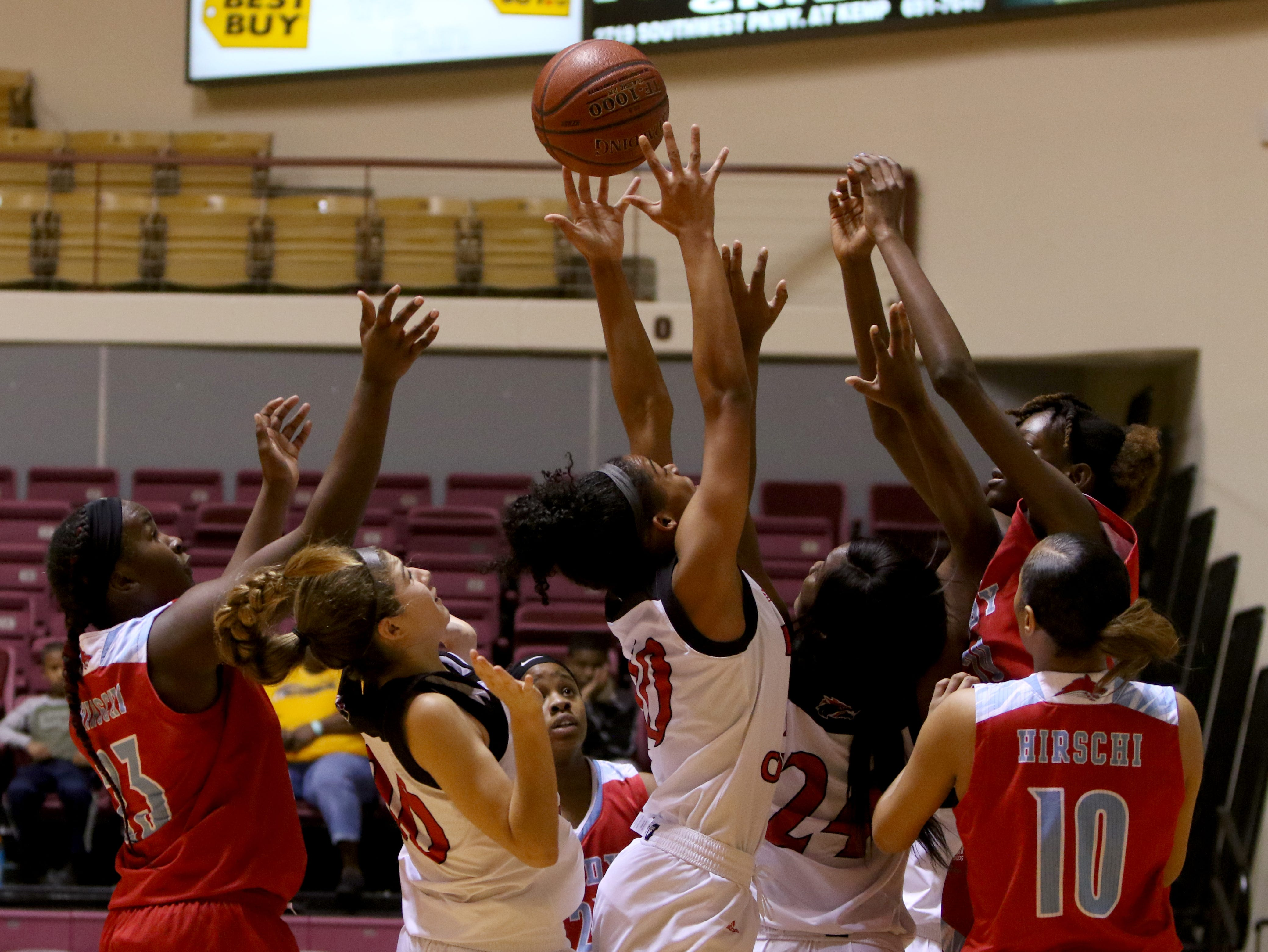 Hirschi and Wichita Falls High School players reach for the rebound Saturday, Dec. 1, 2018, at D.L. Ligon Coliseum at Midwestern State University.