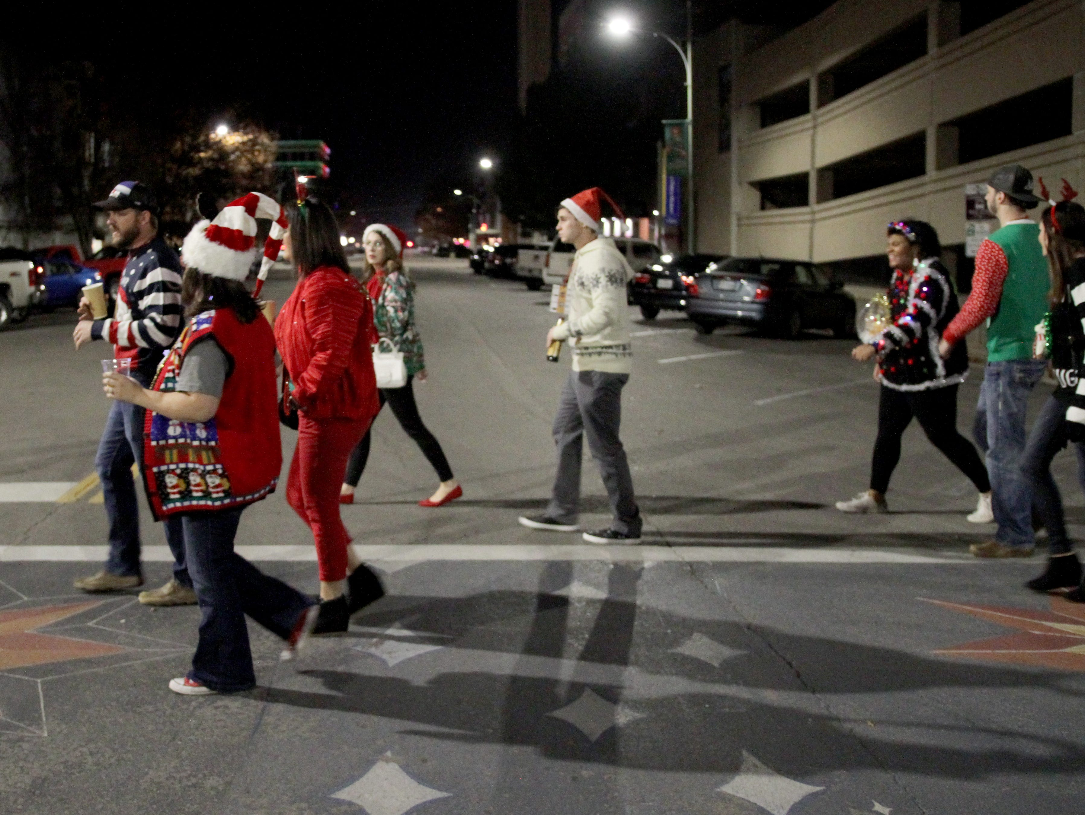 People on Rudolph's First Ugly Sweater Crawl head to their next stop at the Wichtia Falls Brewing Company Saturday, Dec. 1, 2018, in Downtown Wichita Falls.