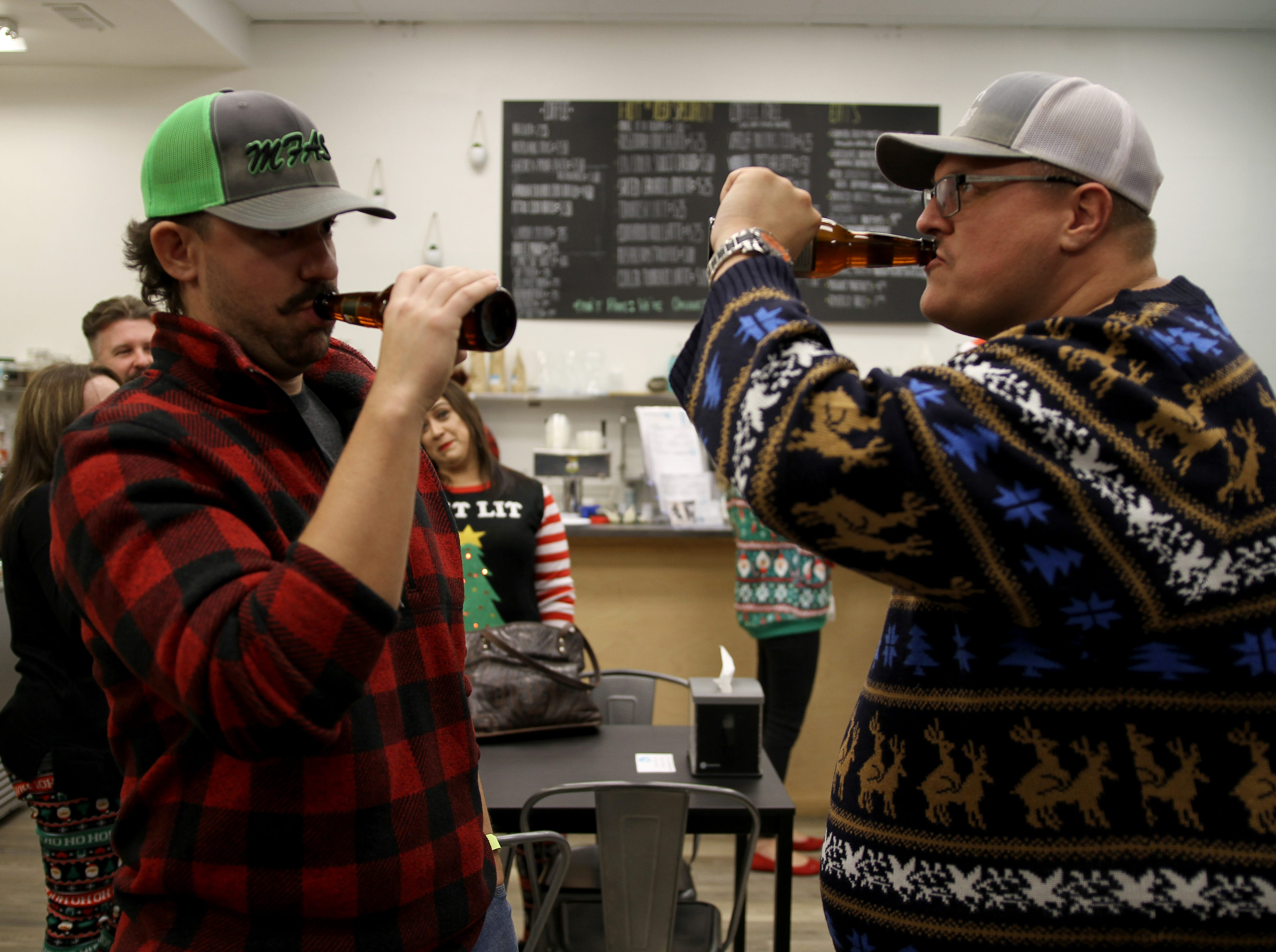Ross Hammond. left, and Jason Templeton drink on Rudolph's First Ugly Sweater Crawl Saturday, Dec. 1, 2018, in Odd Duck Coffee.