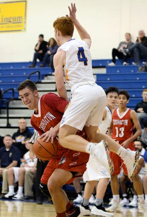Kameron Brown, left, draws contact from West Muskingum's Justin Slater during Coshocton's 55-52 win on Saturday night at Gary Ankrum Gymnasium.