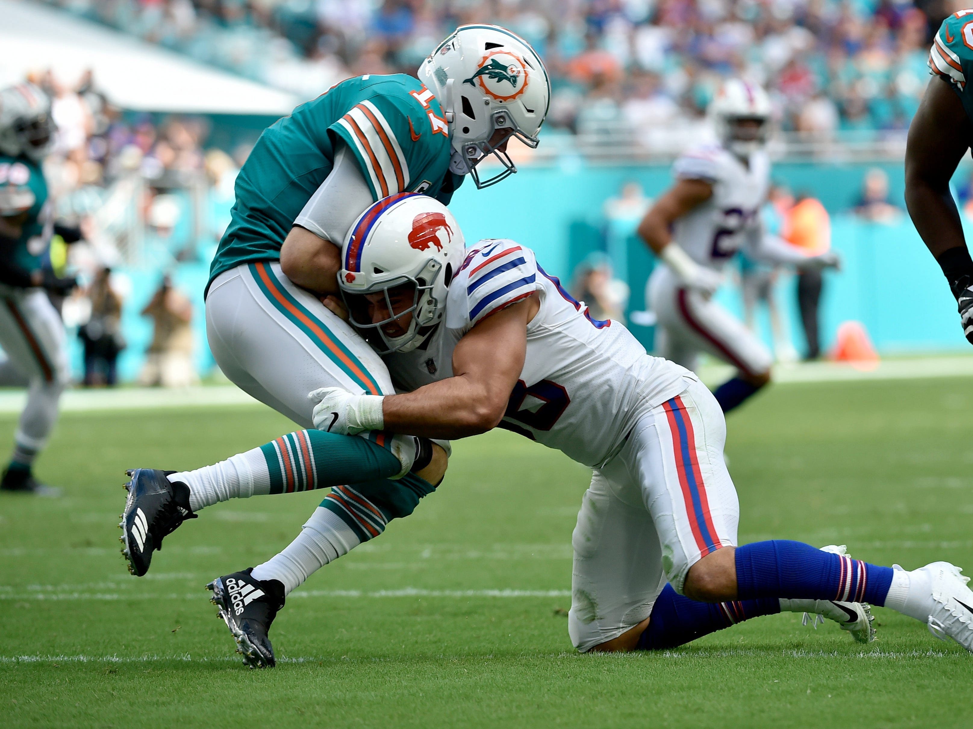 Buffalo Bills outside linebacker Matt Milano (58) tackles Miami Dolphins quarterback Ryan Tannehill (17) during the first half at Hard Rock Stadium.